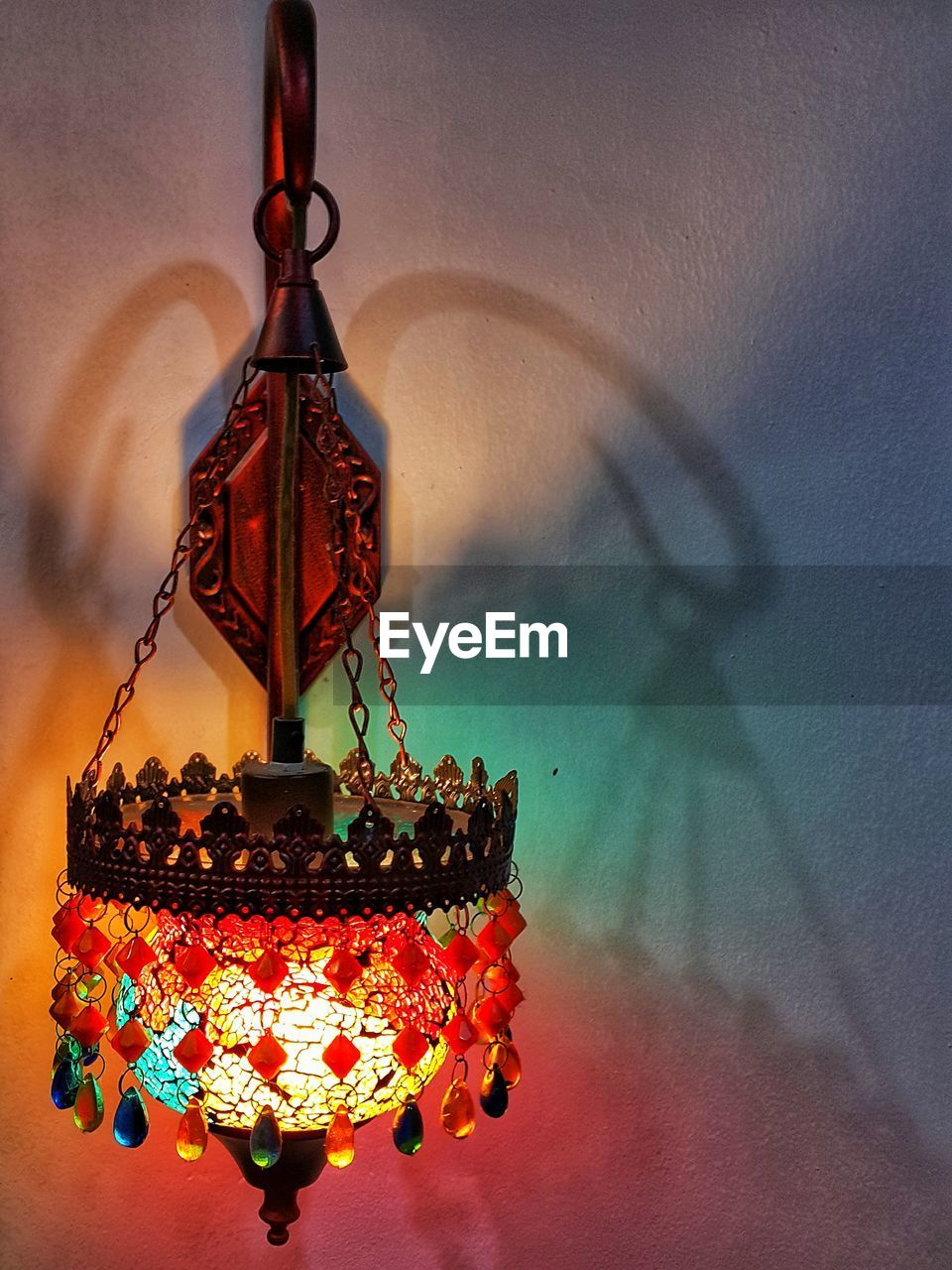 hanging, no people, illuminated, lighting equipment, decoration, wall - building feature, indoors, multi colored, blurred motion, nature, close-up, art and craft, sky, shadow, focus on foreground, red, sunset, craft, rainbow, ceiling, ornate, electric lamp