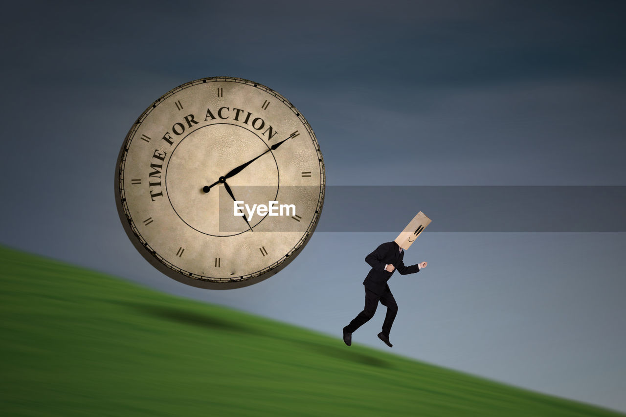 Side view of businessman with obscured face running by clock against sky