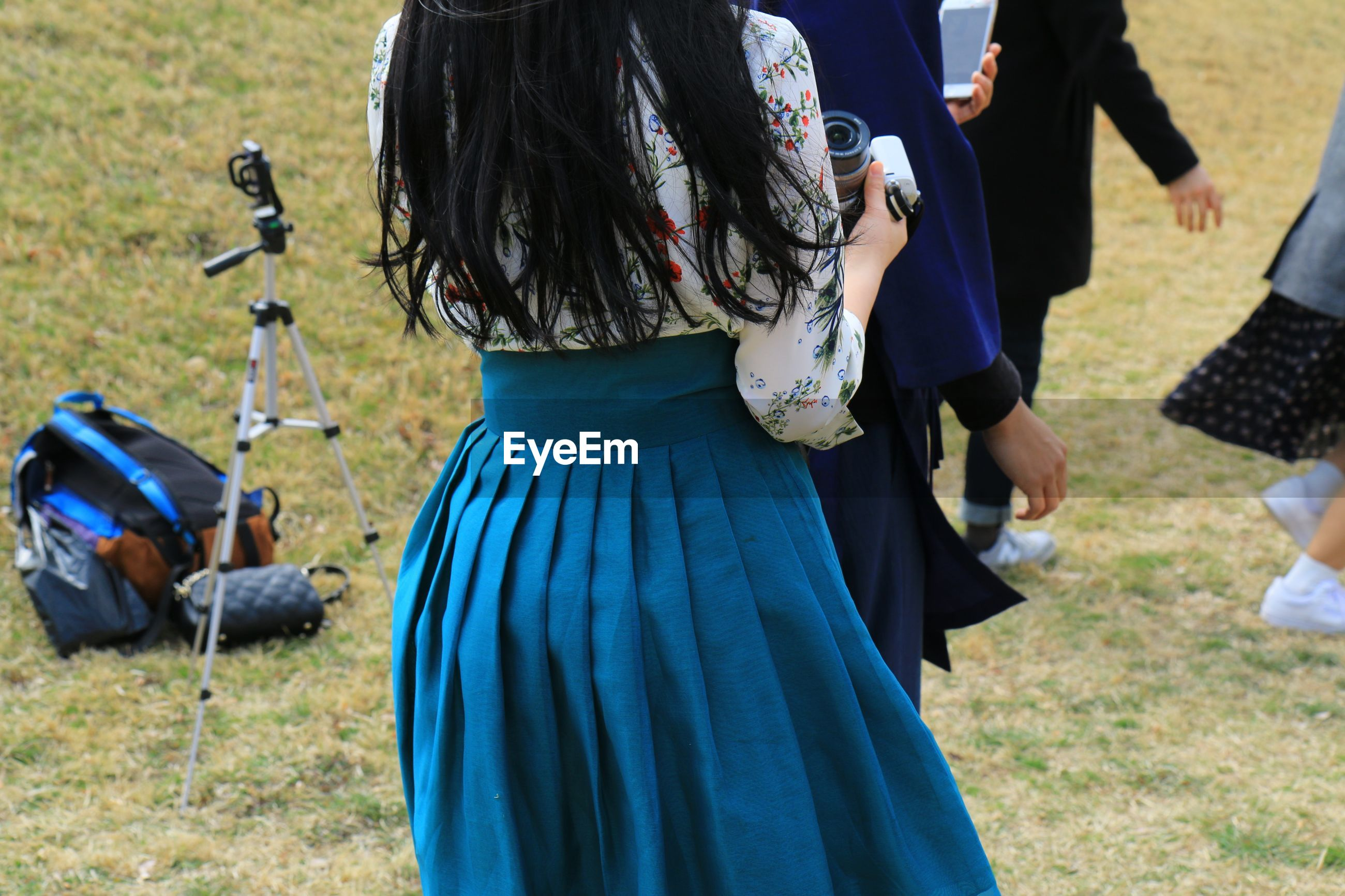 Midsection of woman holding camera while standing by people on field