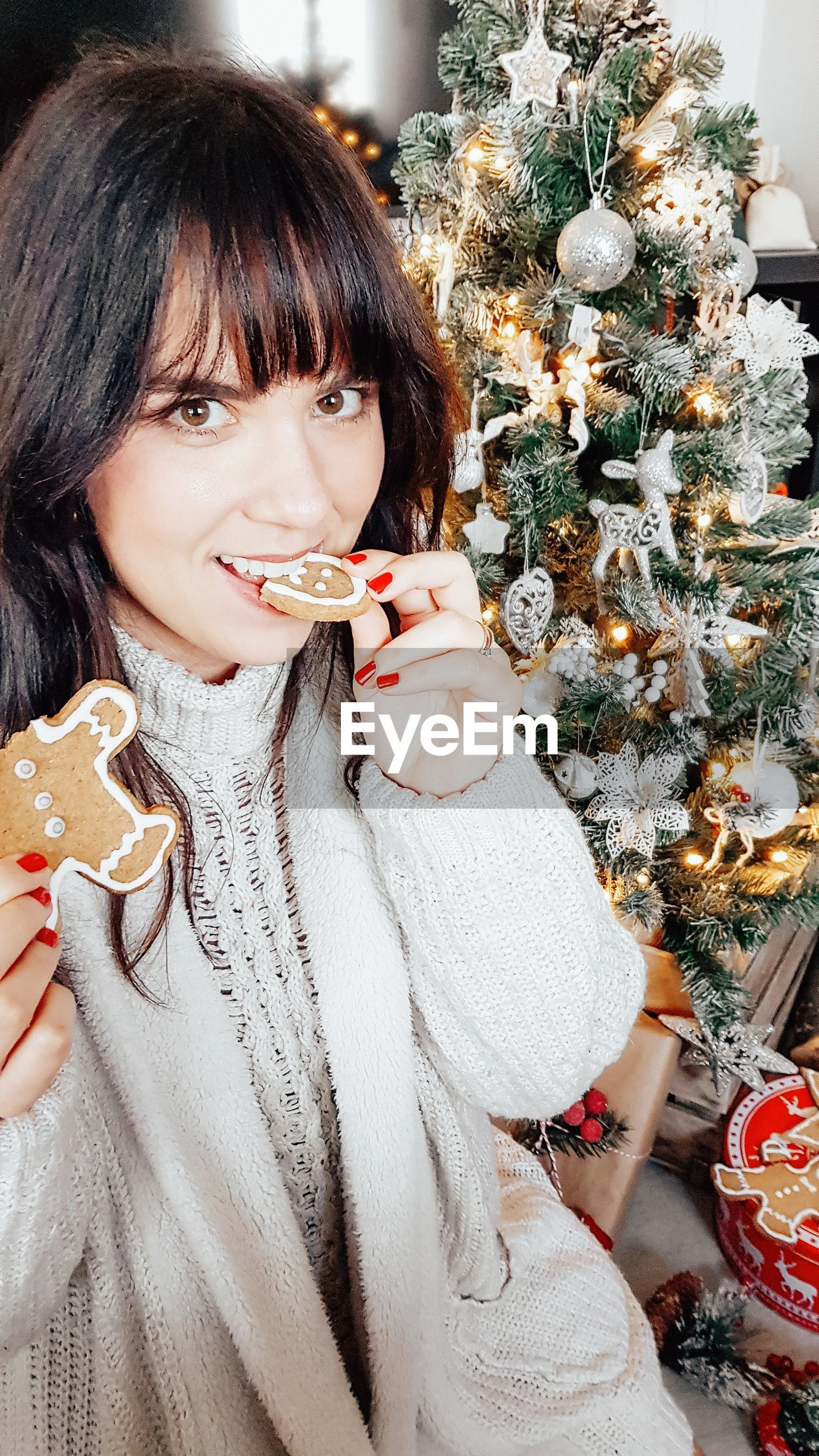 Portrait of woman eating gingerbread by christmas tree