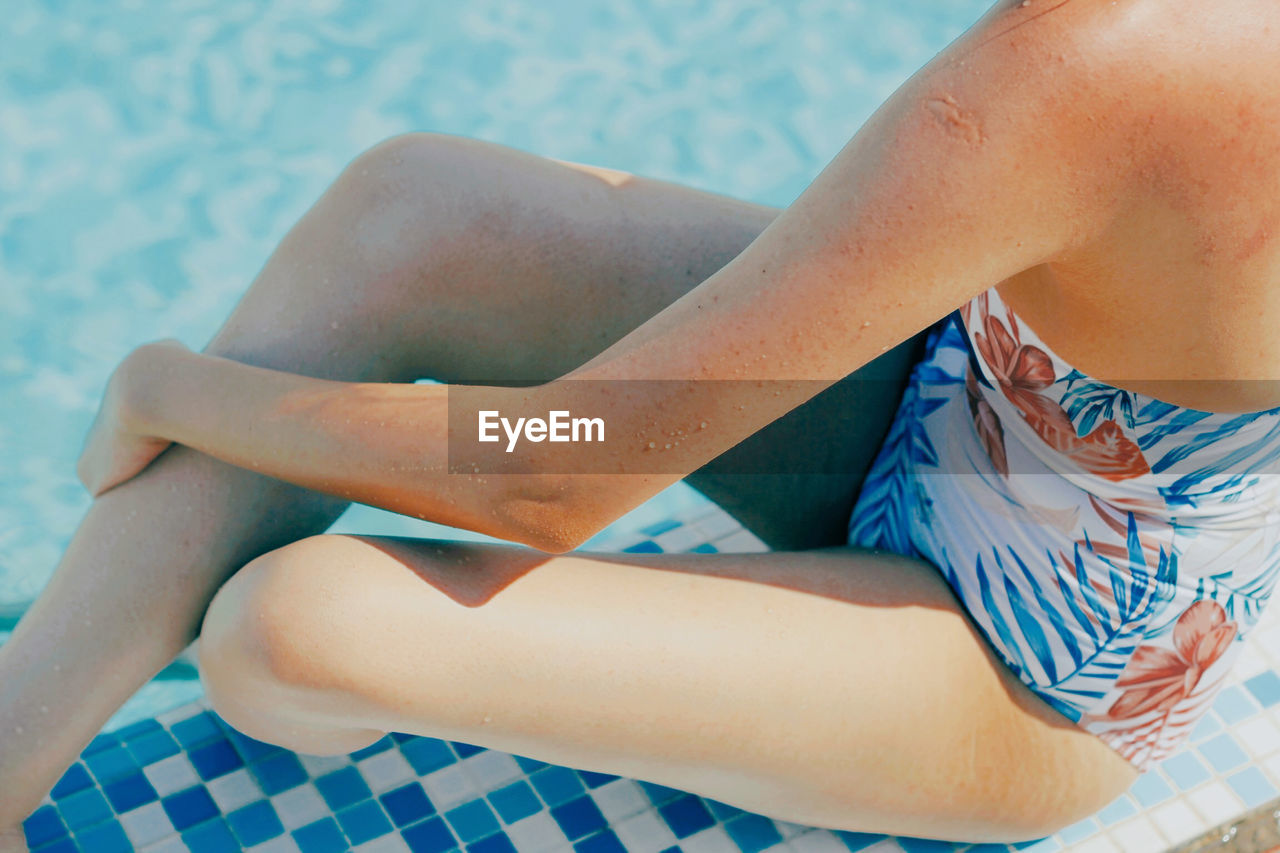 Low section of woman sitting in swimming pool