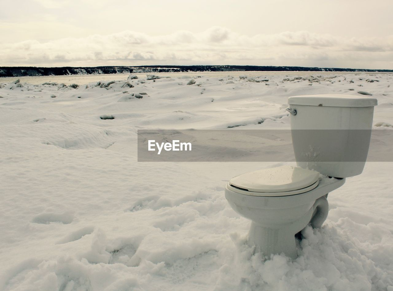 Toilet bowl on snow covered field against sky