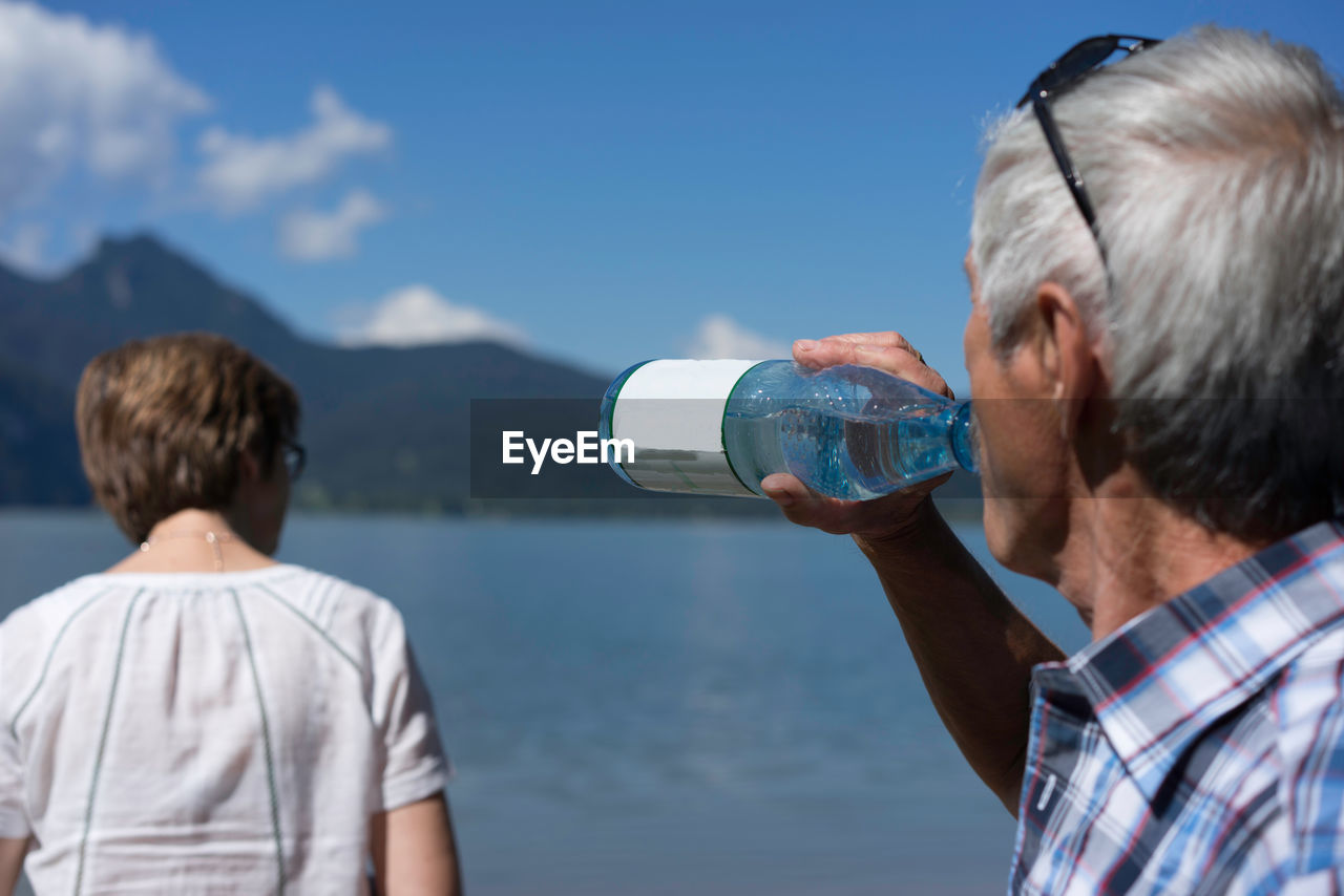 Senior Man Drinking Water By Woman Near Kocher Lake Against Sky