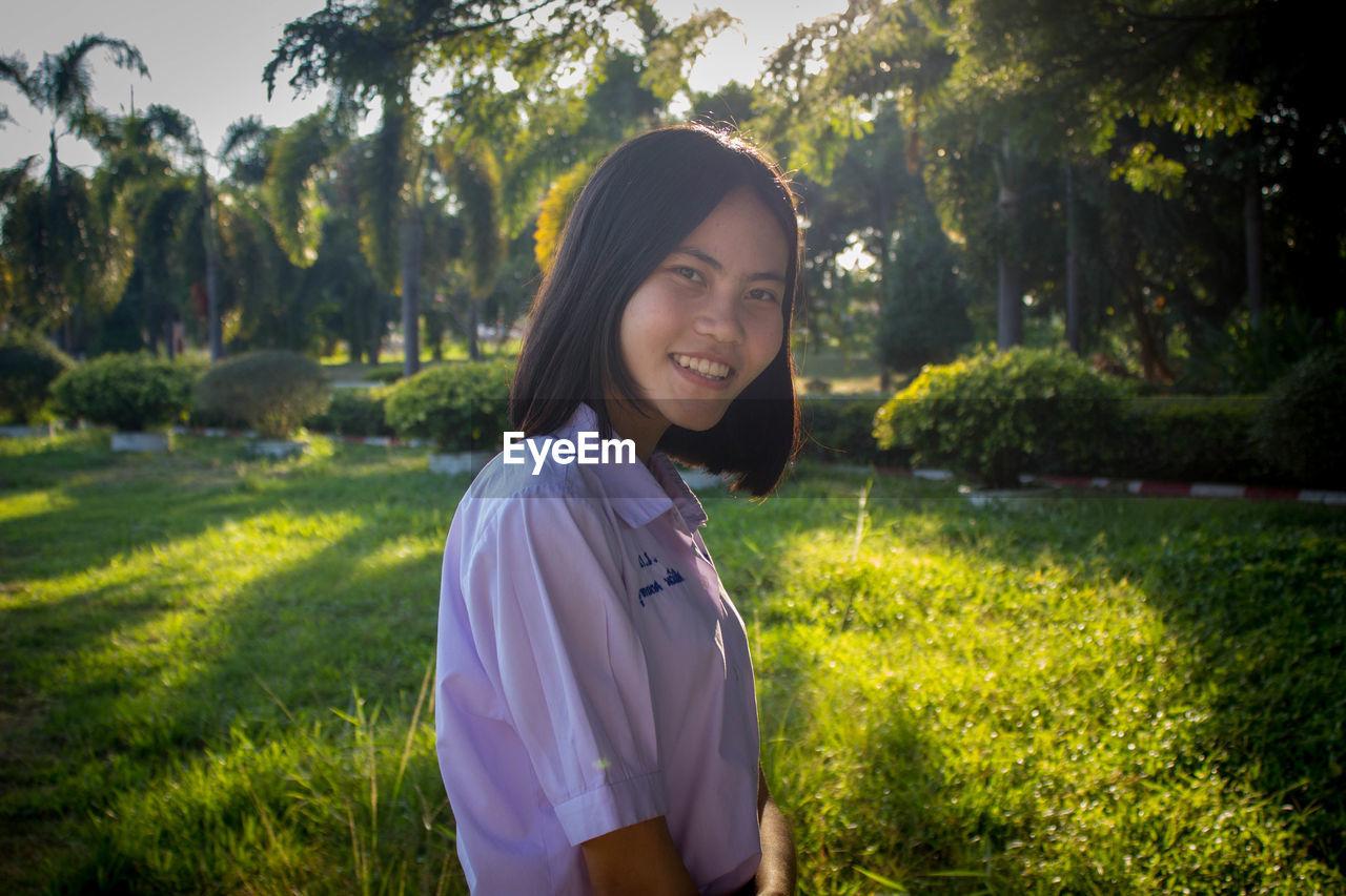 Portrait Of Smiling Teenage Girl Standing On Field