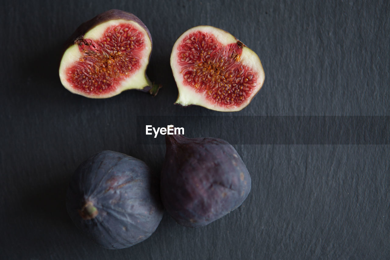healthy eating, wellbeing, fruit, freshness, food and drink, food, fig, still life, no people, indoors, cross section, close-up, high angle view, table, group of objects, studio shot, slice, directly above, three objects, halved, ripe, purple
