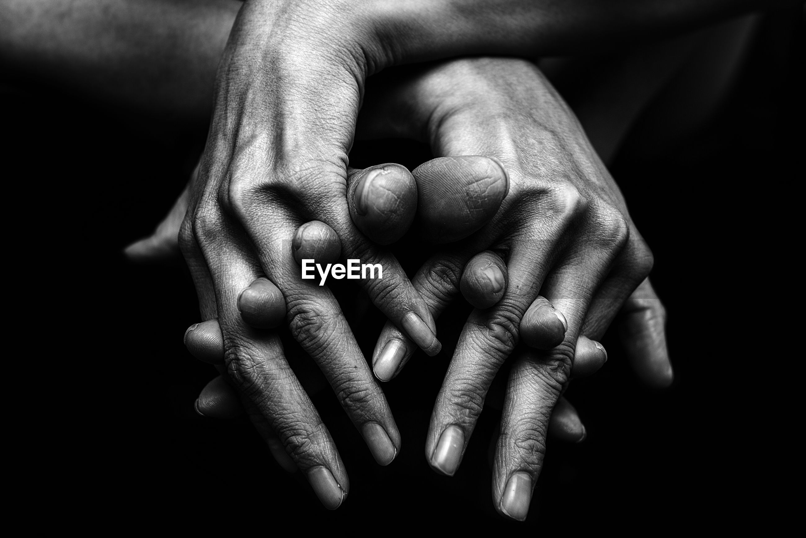 Cropped image of hands against black background