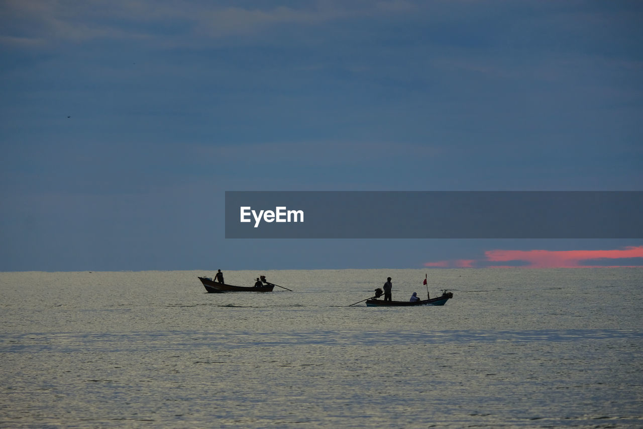 PEOPLE IN BOAT SAILING ON SEA AGAINST SKY