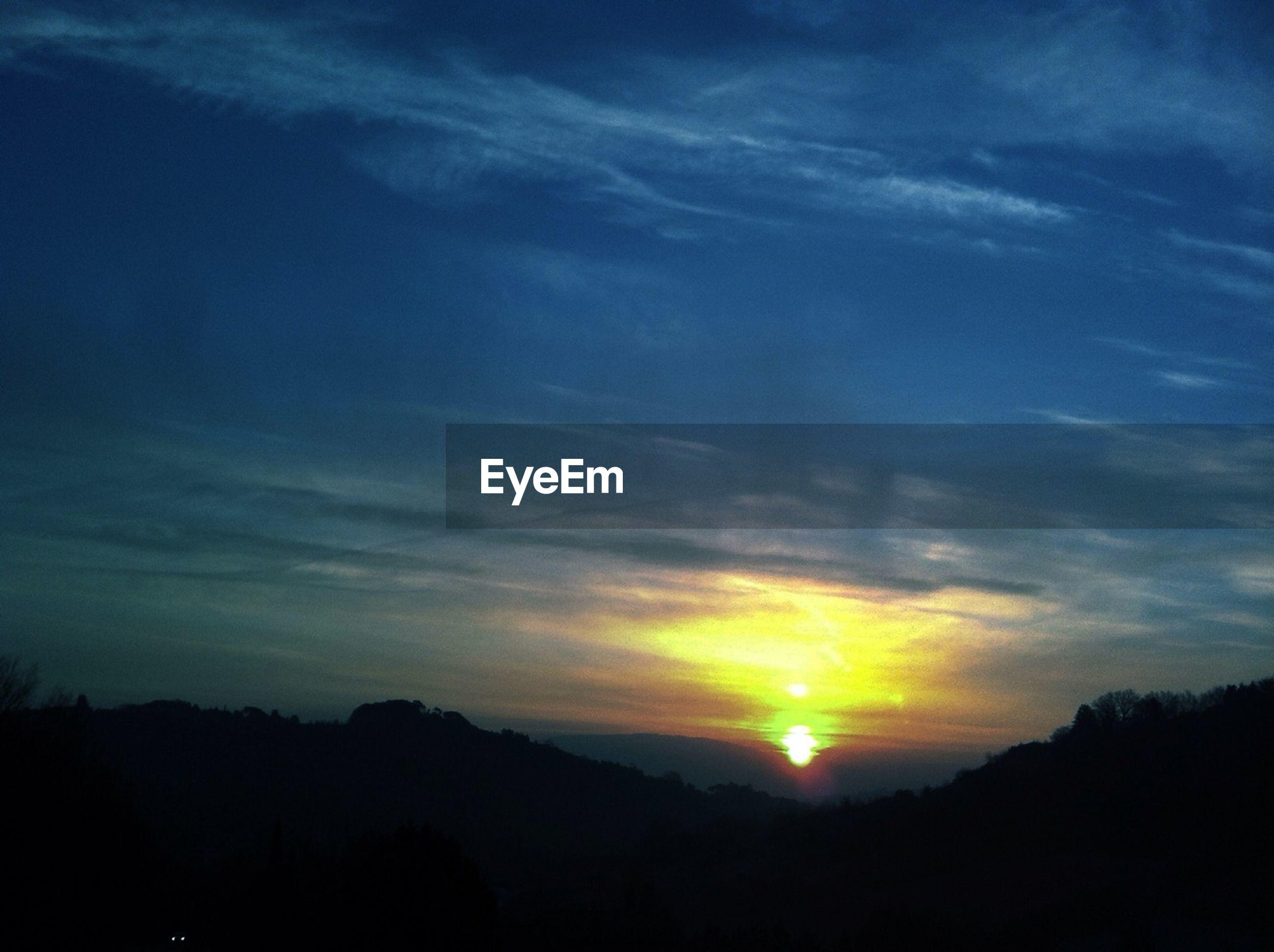 sunset, silhouette, scenics, tranquil scene, sky, beauty in nature, tranquility, sun, idyllic, cloud - sky, orange color, nature, sunlight, cloud, landscape, tree, outdoors, mountain, sunbeam, majestic