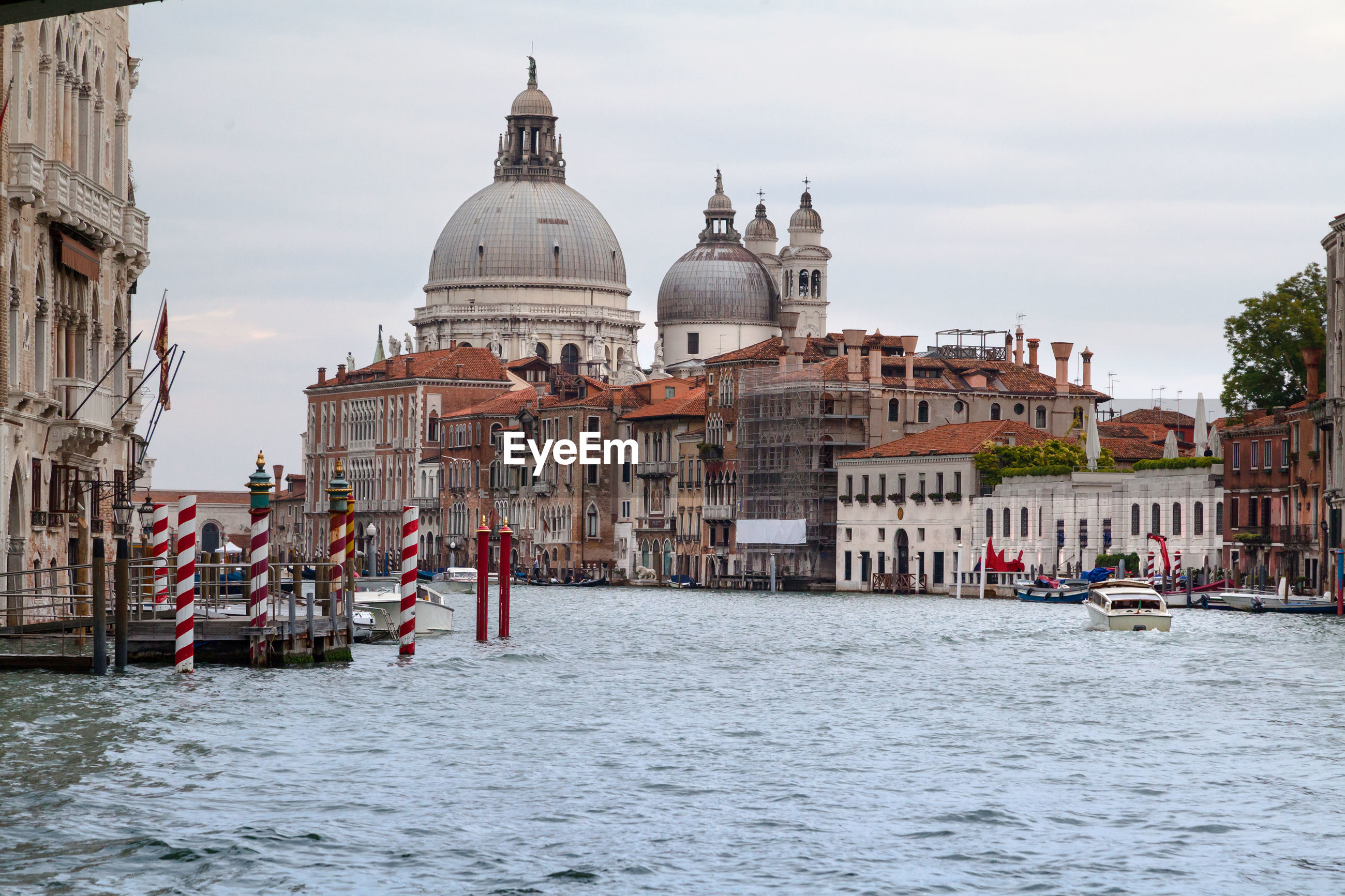 Canal by santa maria della salute in city against sky