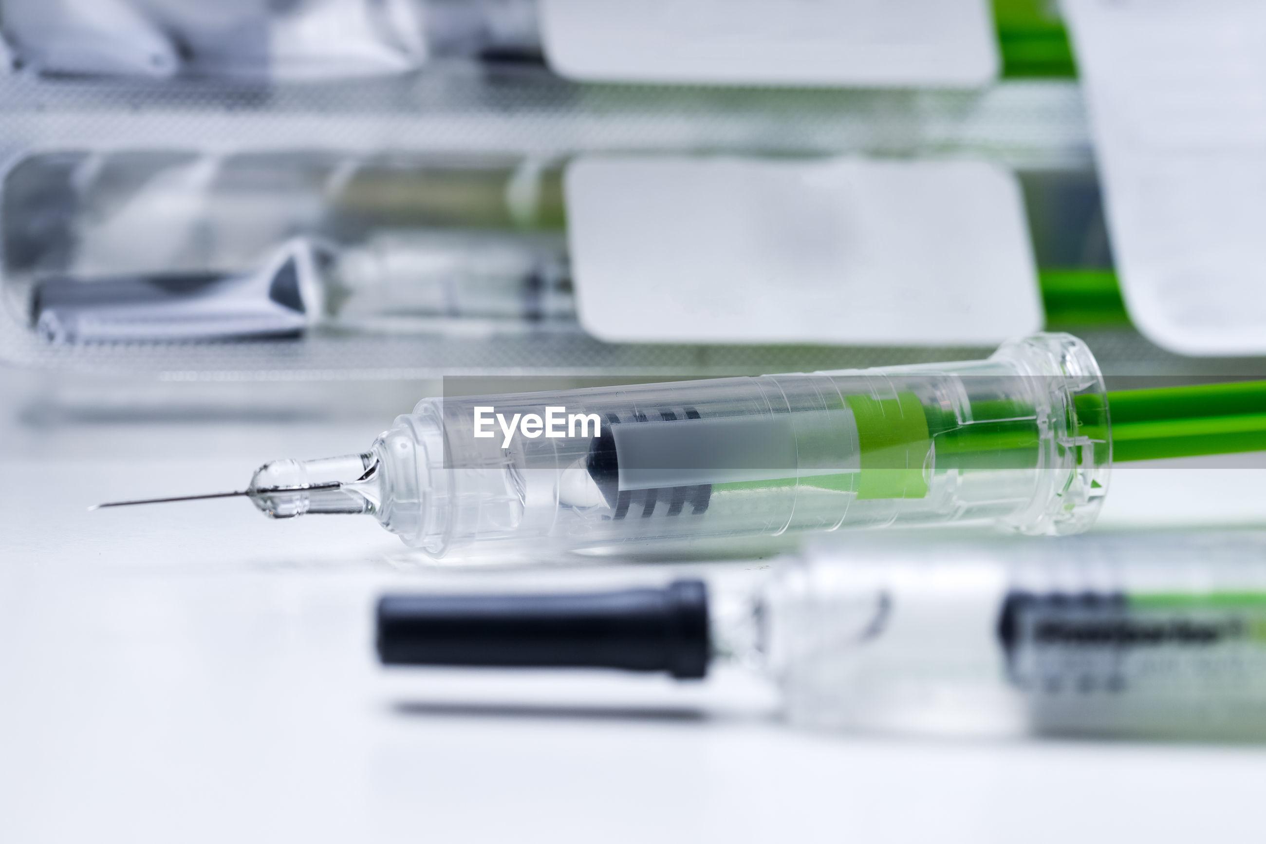Close-up of syringe at desk