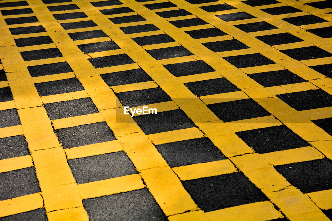 full frame, backgrounds, yellow, pattern, high angle view, no people, road marking, marking, black color, striped, sign, symbol, flooring, road, asphalt, safety, textured, close-up, transportation, street, outdoors, tiled floor