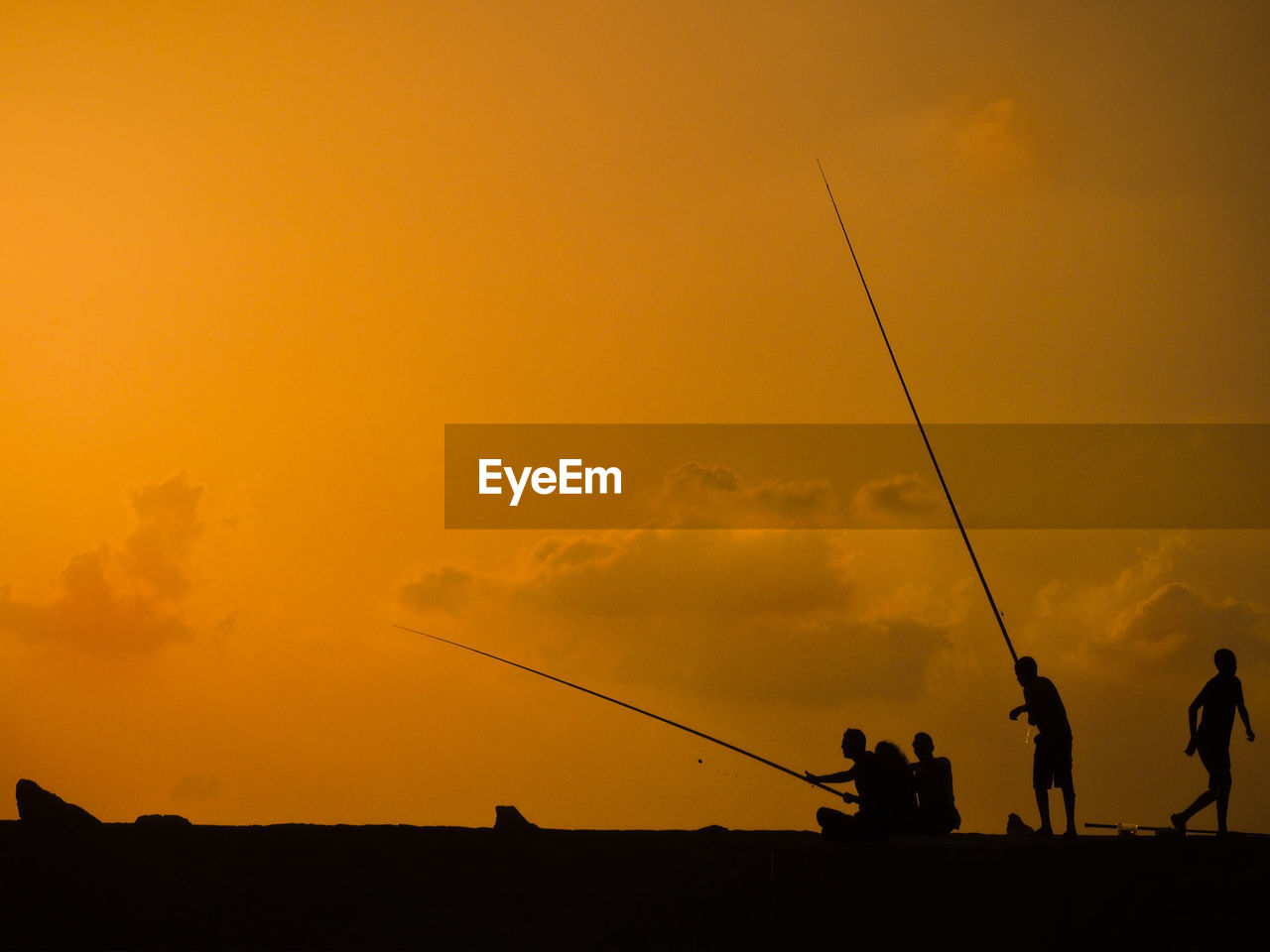 sunset, sky, silhouette, orange color, real people, men, fishing rod, cloud - sky, rod, fishing, group of people, nature, leisure activity, activity, lifestyles, beauty in nature, people, outdoors, scenics - nature, occupation, fisherman