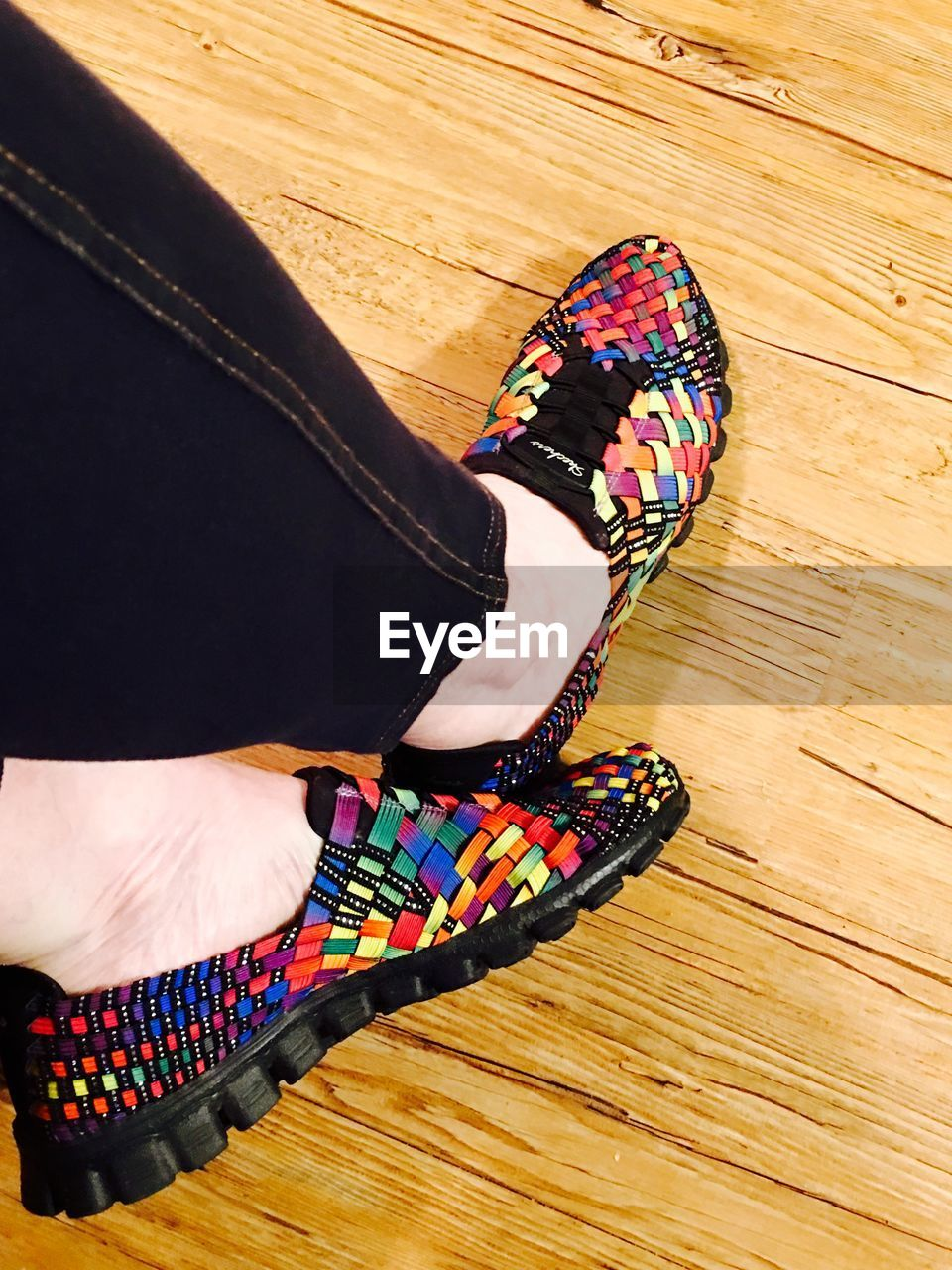 Low section of woman wearing multi colored shoes on hardwood floor