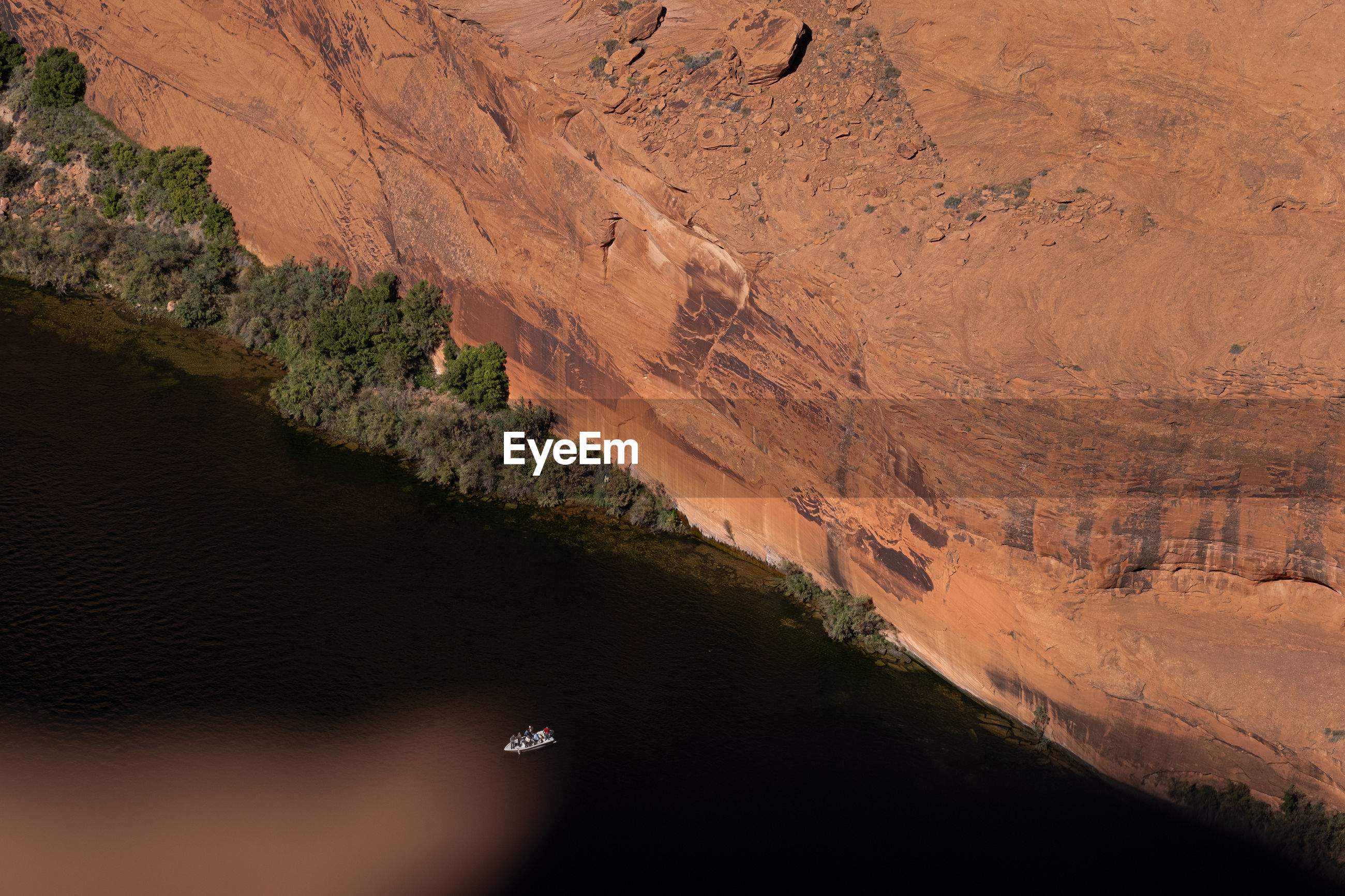 High angle view of small boat on colorado river against red cliff in arizona, usa