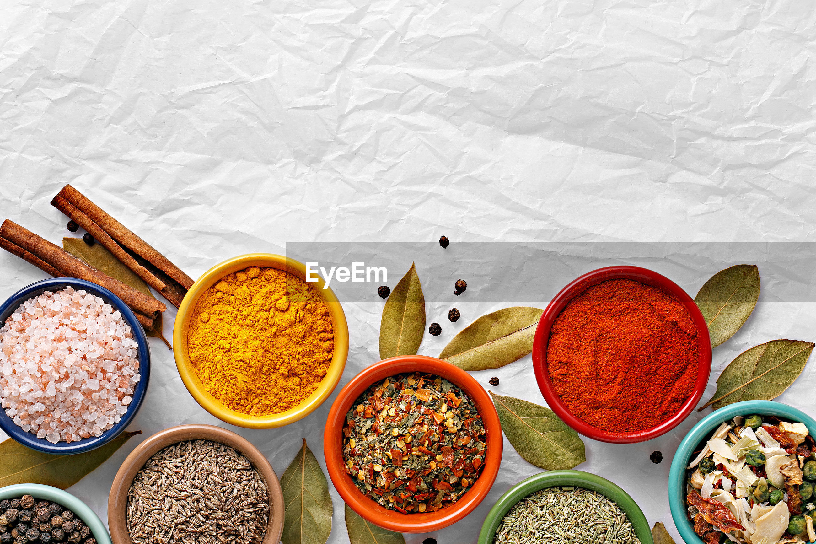 Directly above shot of spices in bowl on white paper