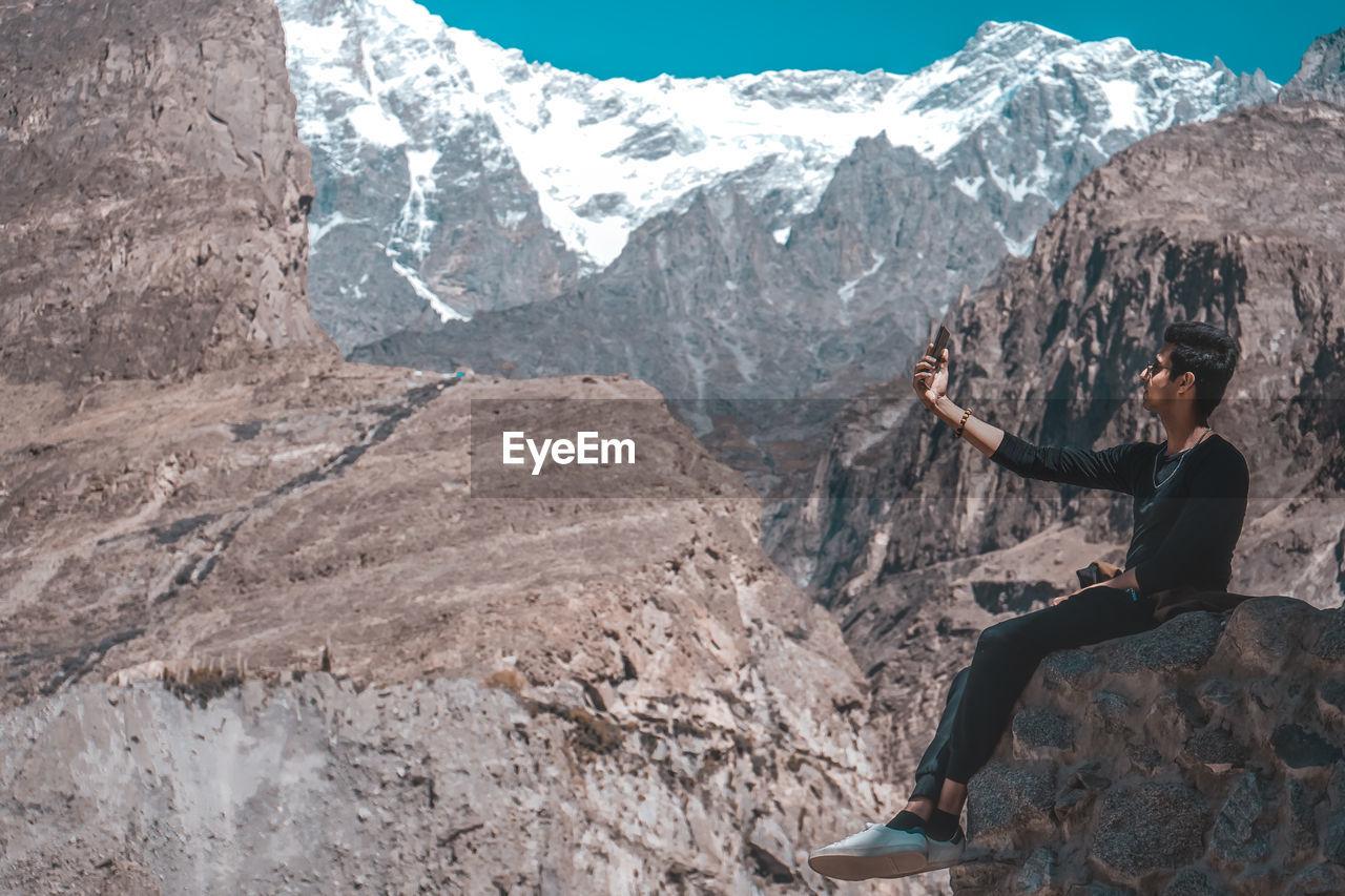 Man taking selfie while sitting on mountain