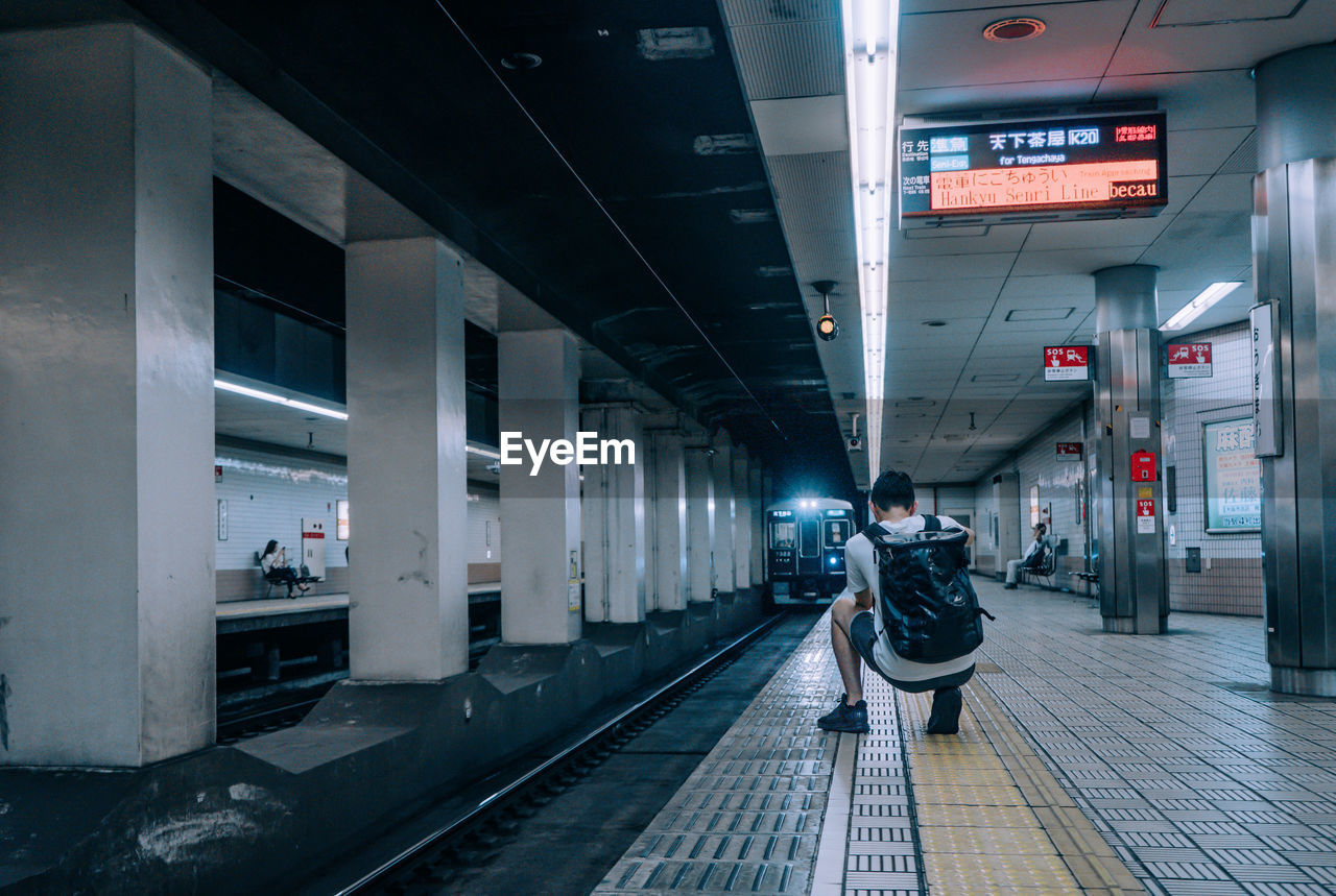 transportation, rail transportation, mode of transportation, real people, one person, public transportation, travel, full length, architecture, track, railroad track, illuminated, indoors, men, built structure, lifestyles, railroad station platform, standing, architectural column, waiting, ceiling