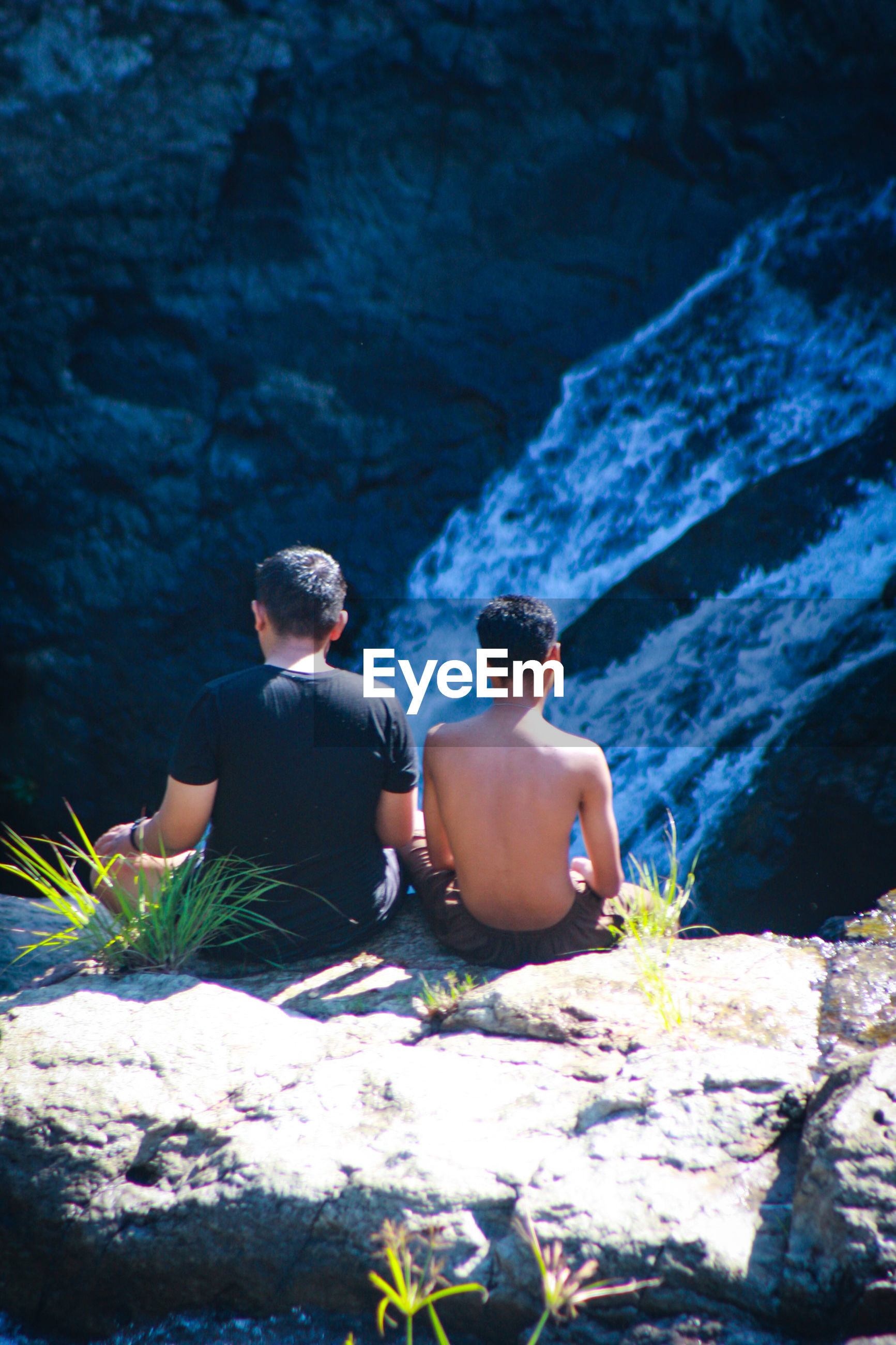 Rear view of male friends sitting on cliff against waterfall