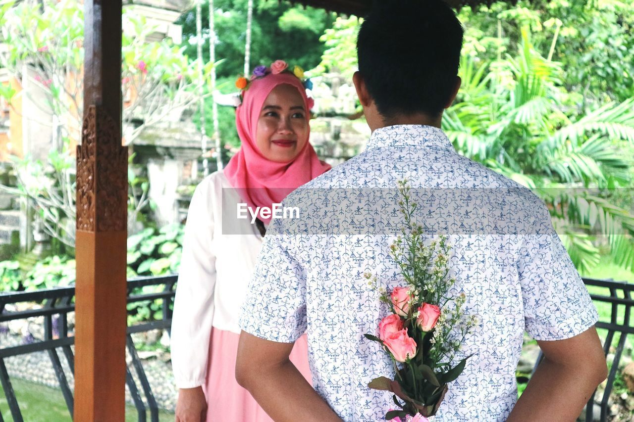 Rear view of man holding flower bouquet with women smiling while standing outdoors