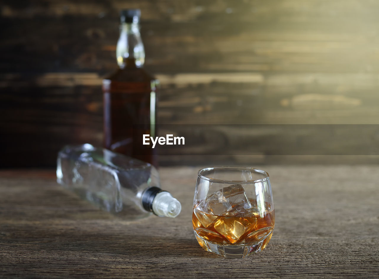 glass - material, transparent, table, glass, drink, drinking glass, food and drink, refreshment, still life, alcohol, household equipment, focus on foreground, whiskey, no people, indoors, close-up, wood - material, bottle, container