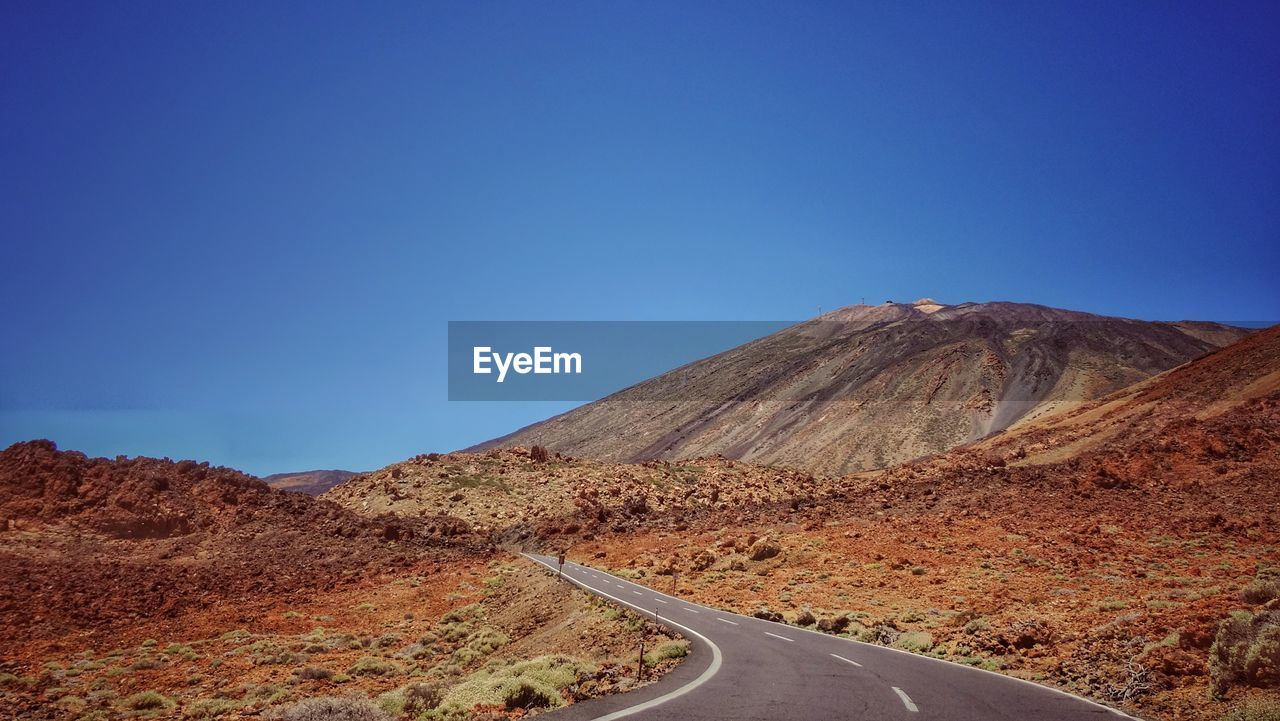 road, mountain, clear sky, nature, tranquil scene, scenics, tranquility, blue, transportation, landscape, beauty in nature, the way forward, non-urban scene, copy space, remote, empty, physical geography, day, no people, outdoors, mountain range, arid climate, winding road, desert, mountain road, sky