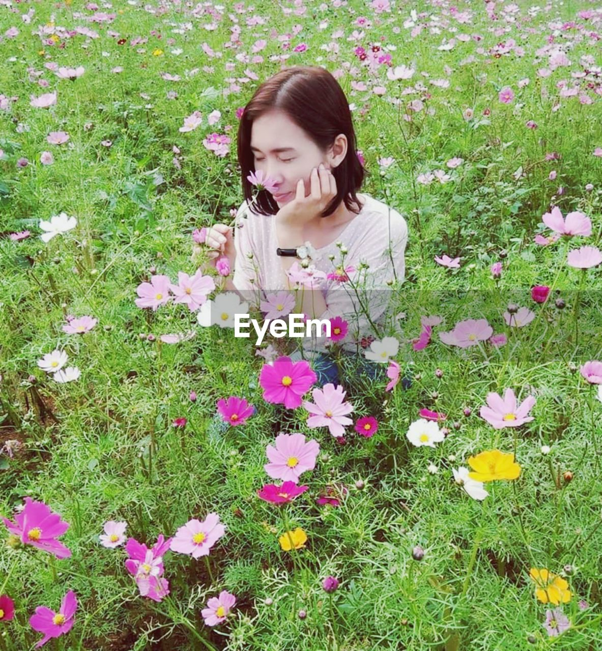 WOMAN WITH PINK FLOWER IN FIELD