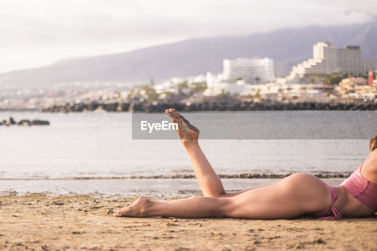Low section of seductive young woman lying at beach