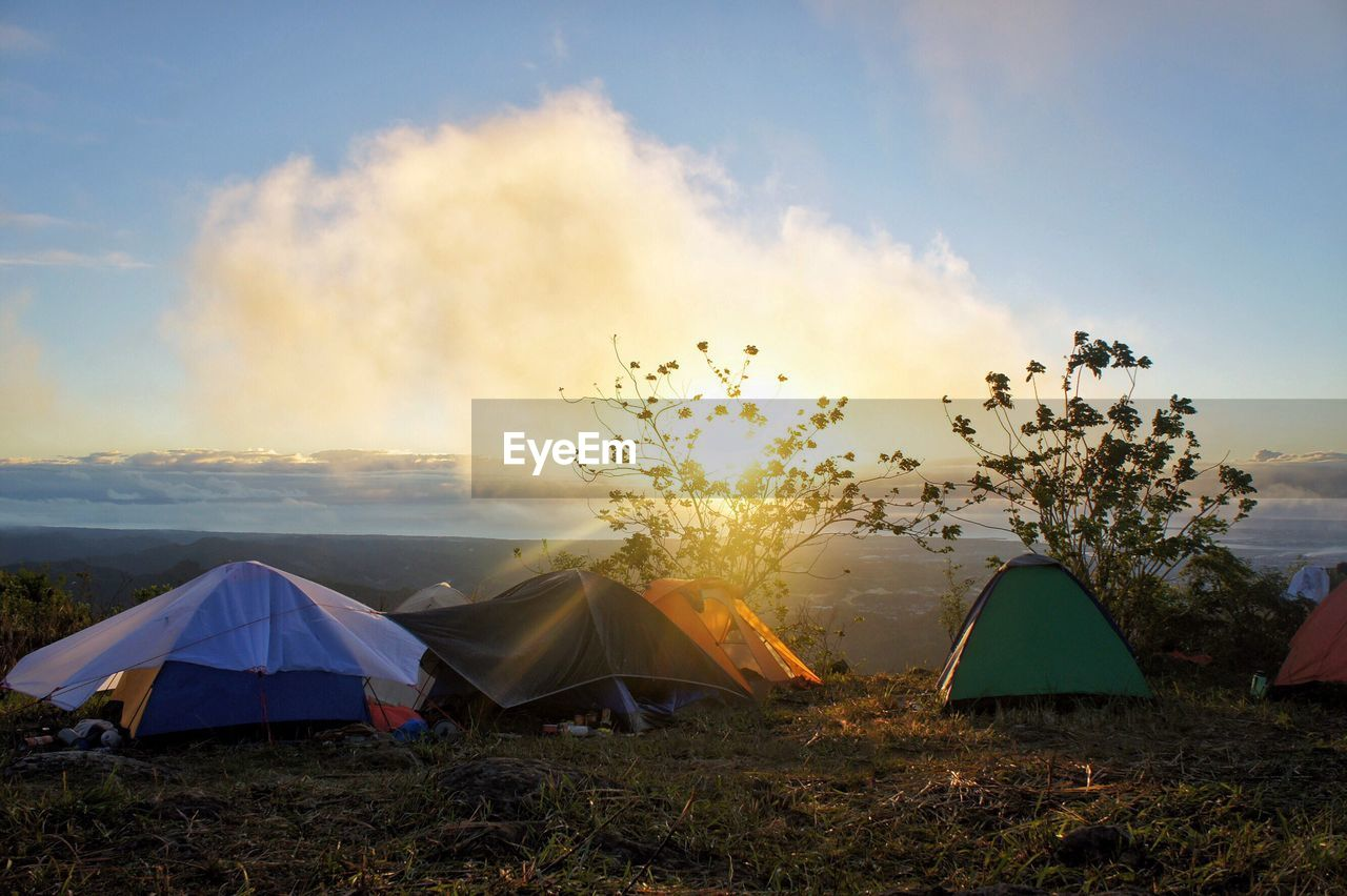 sky, tent, beauty in nature, sunset, nature, camping, cloud - sky, land, plant, field, landscape, scenics - nature, tranquility, outdoors, no people, grass, tranquil scene, environment, sunlight, non-urban scene