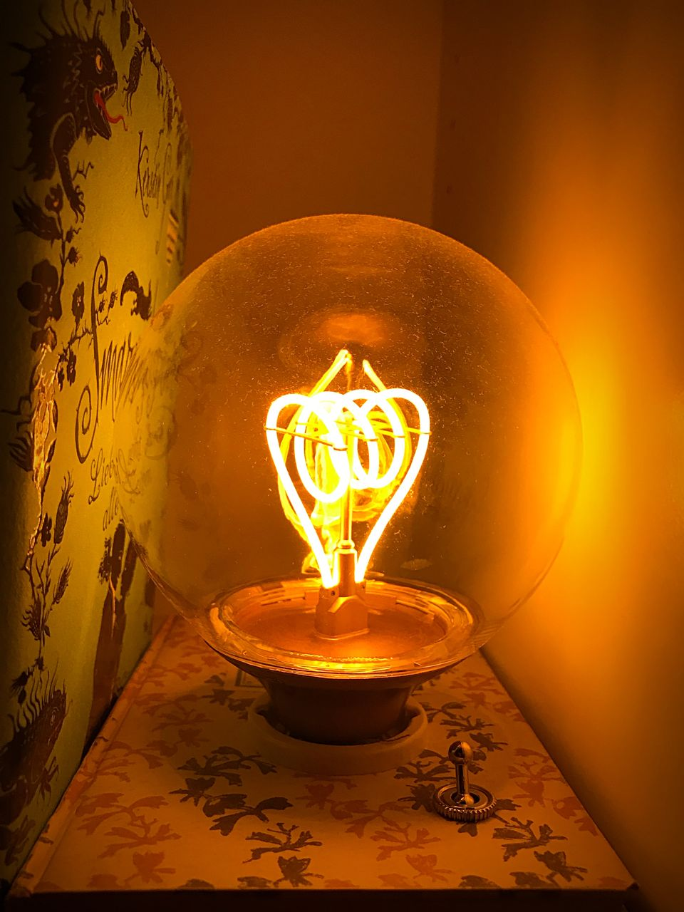 illuminated, lighting equipment, indoors, glowing, burning, fire, close-up, electricity, flame, no people, fire - natural phenomenon, light bulb, light, glass - material, candle, heat - temperature, light - natural phenomenon, filament, yellow, orange color, electric lamp, floral pattern