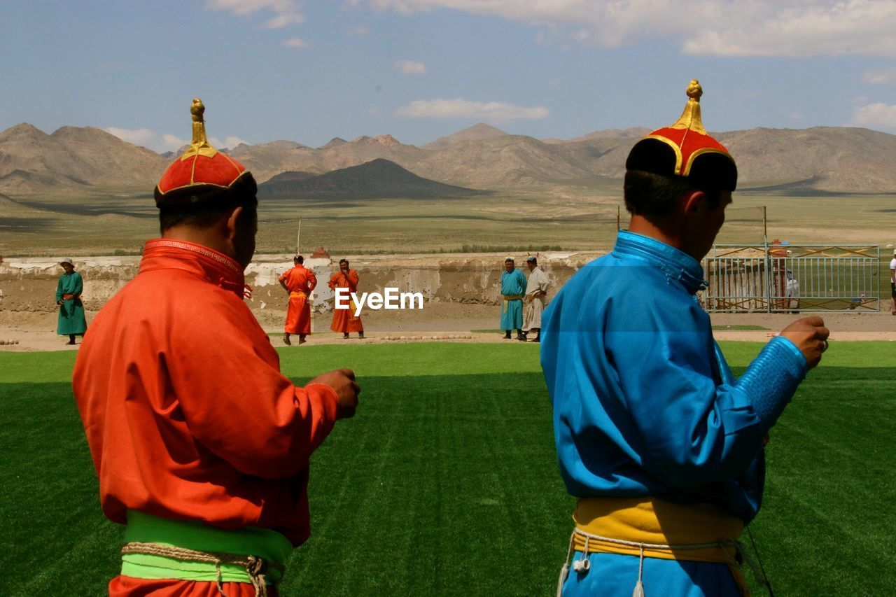 People Playing By Grassy Field Against Mountains