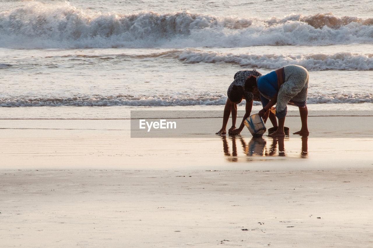 MAN ON BEACH AGAINST SEA