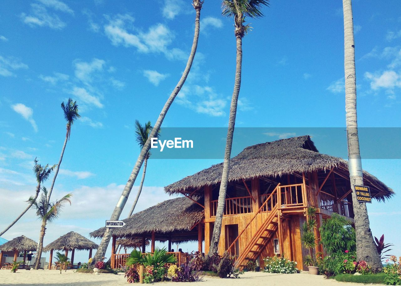 Palm trees growing by traditional building at beach against sky