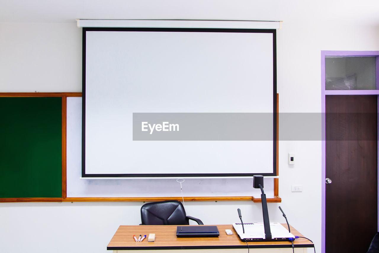 table, indoors, education, furniture, board, seat, no people, copy space, desk, whiteboard, empty, absence, classroom, technology, chair, screen, school, learning, publication, blank