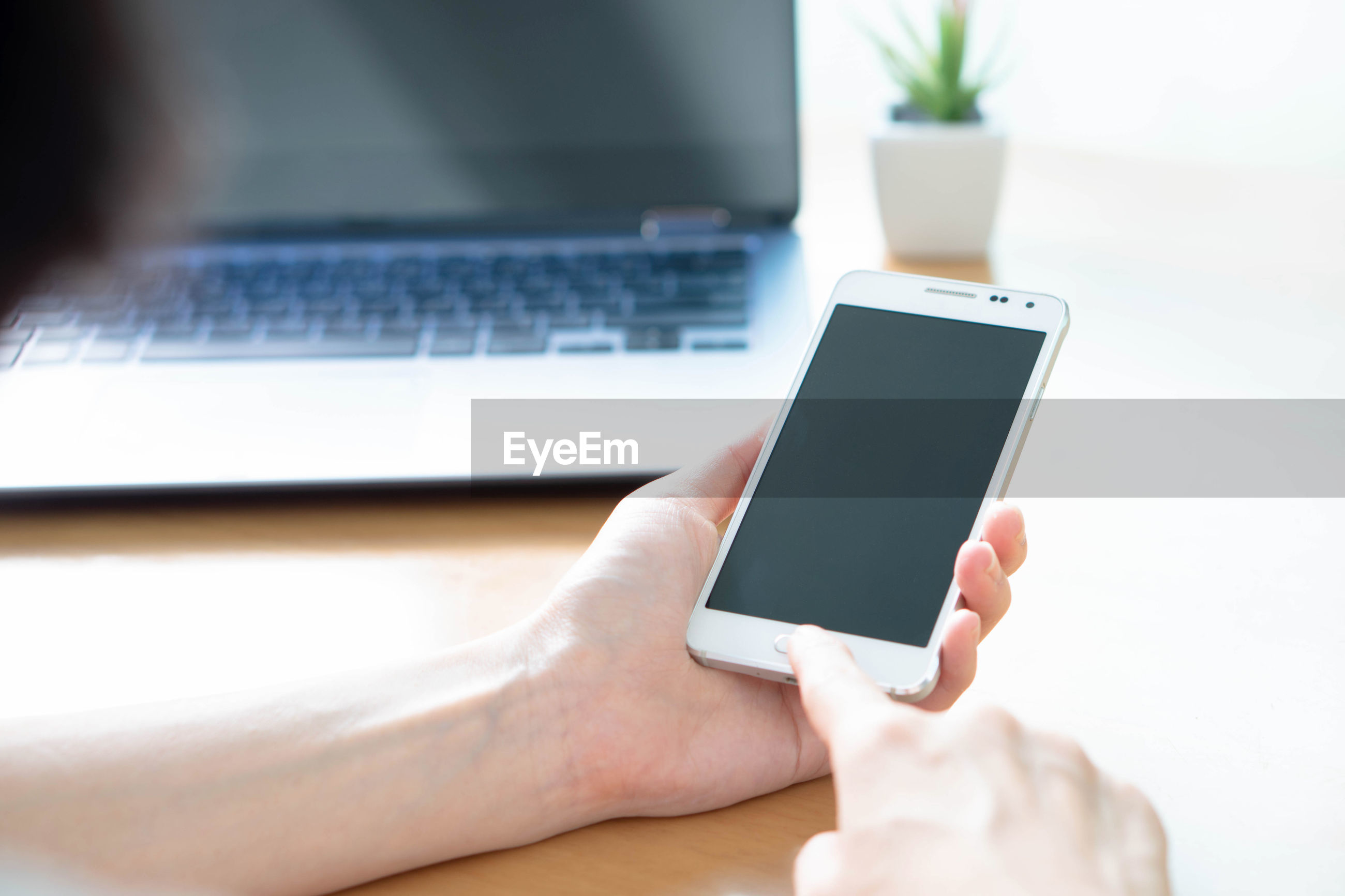 Cropped hand of person using mobile phone and laptop on table