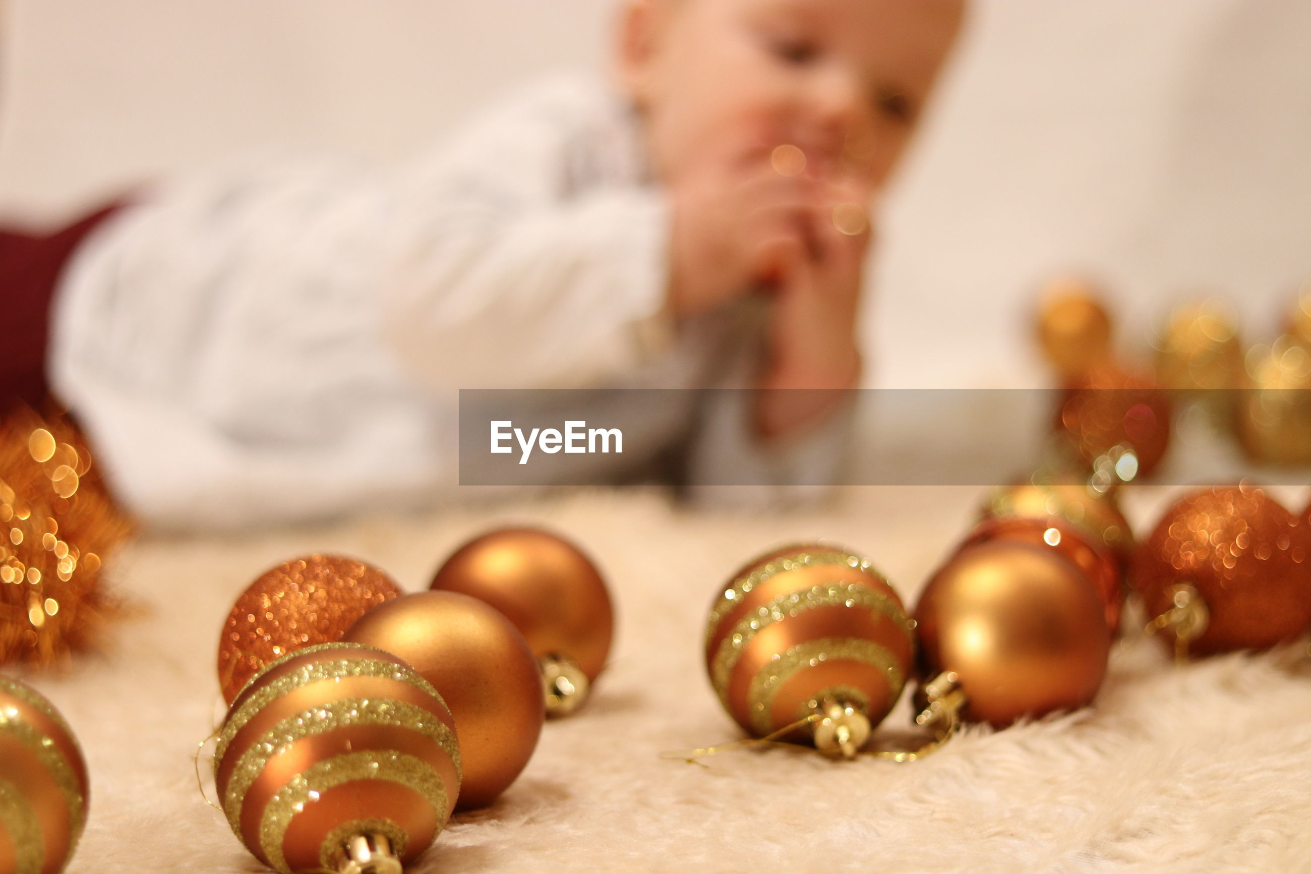 Close-up of baubles with girl lying on rug