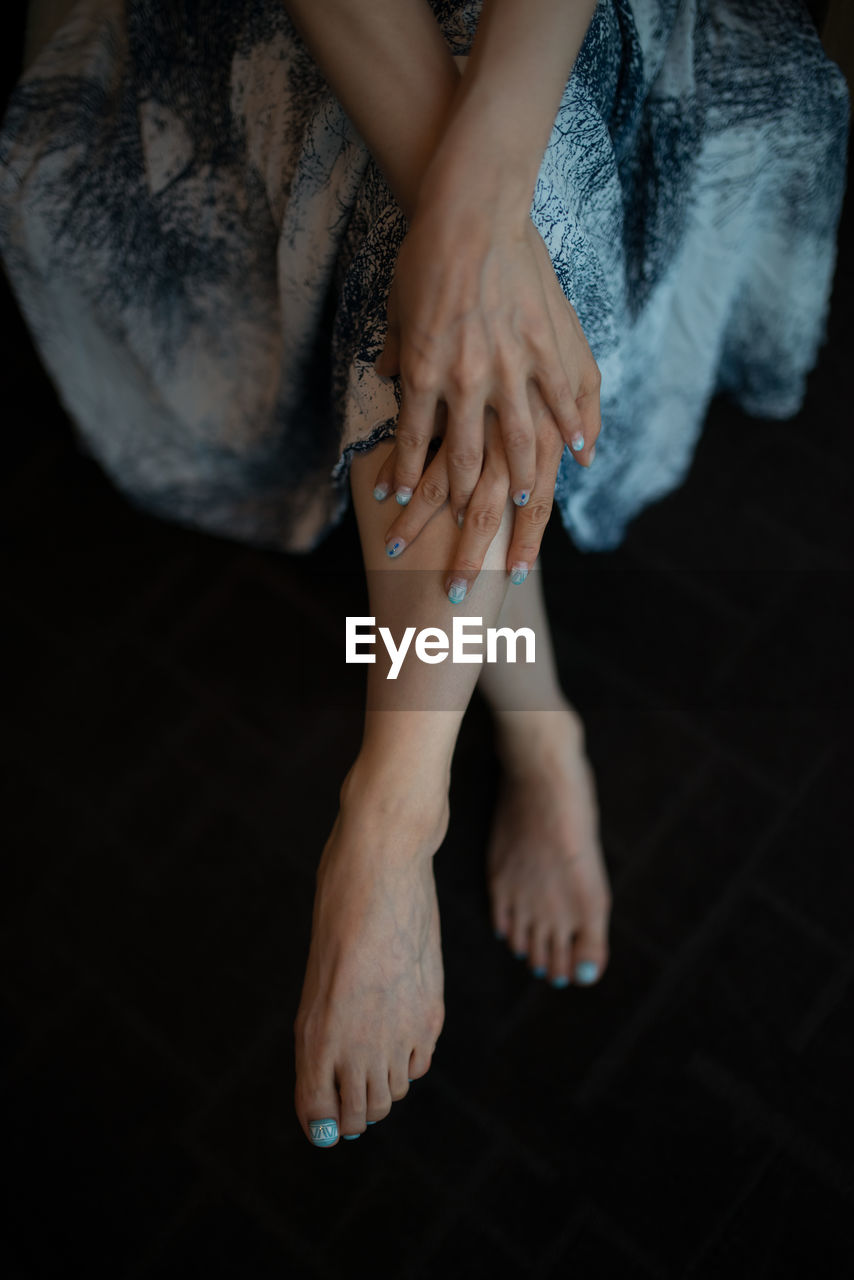 one person, human body part, low section, women, human leg, lifestyles, adult, indoors, high angle view, body part, barefoot, real people, sitting, leisure activity, relaxation, nail, beauty, human hand, human foot, human limb, beautiful woman