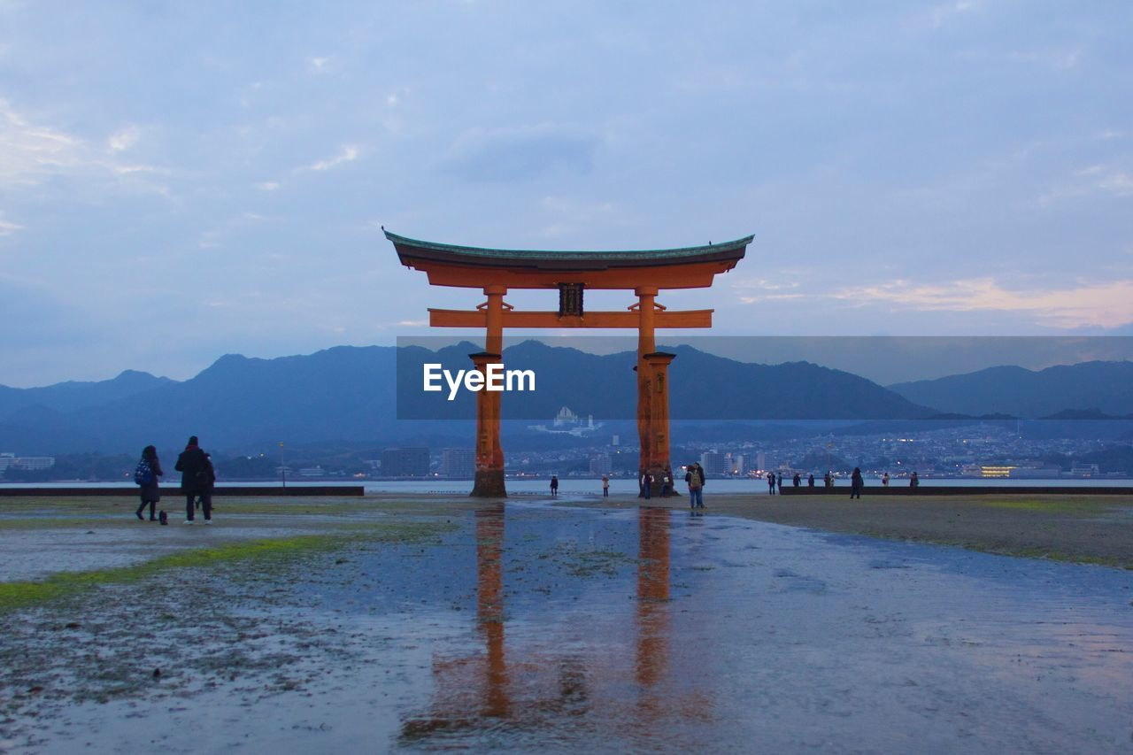 Torii gate against cloudy sky at miyajima island