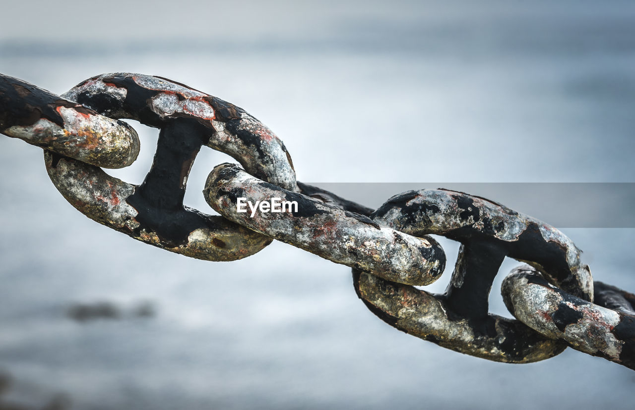 CLOSE-UP OF RUSTY CHAIN AGAINST WATER