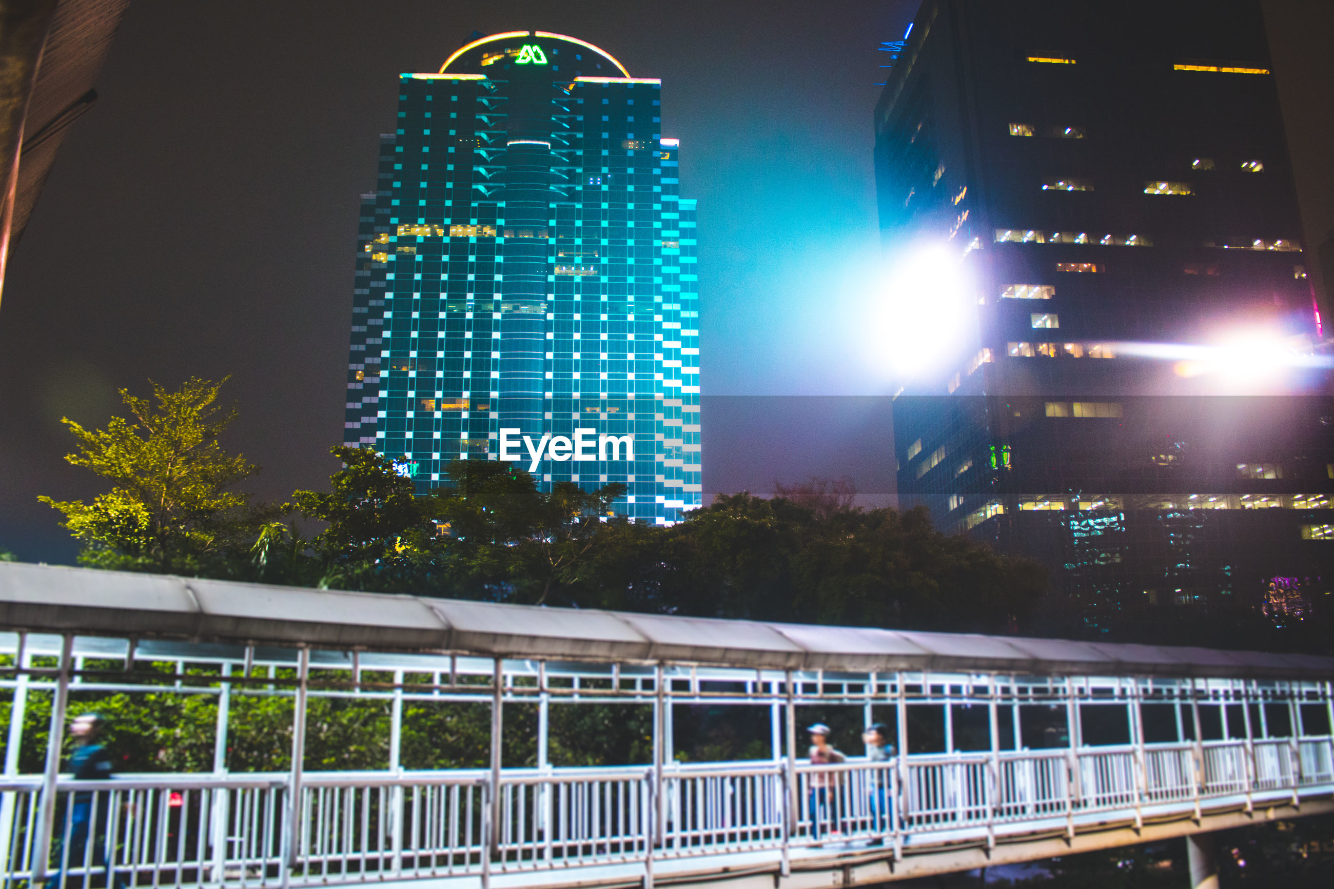 Low angle view of bridge and buildings at night