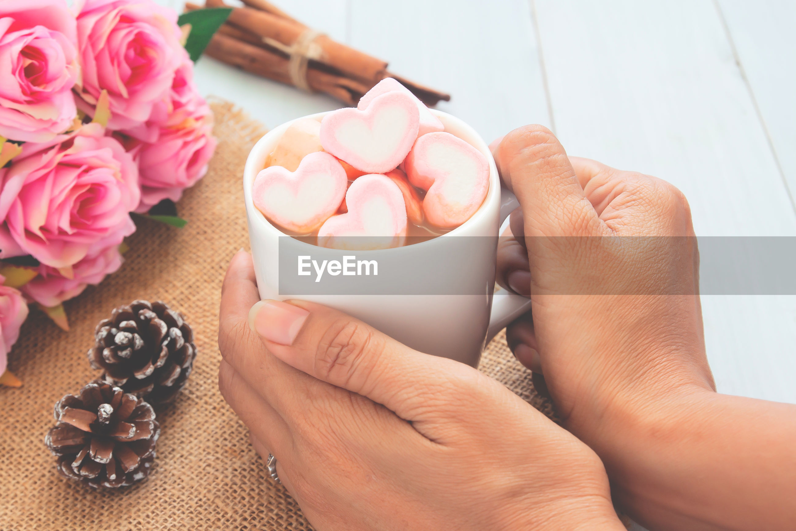 Cropped hand holding cup with heart shape marshmallows on table