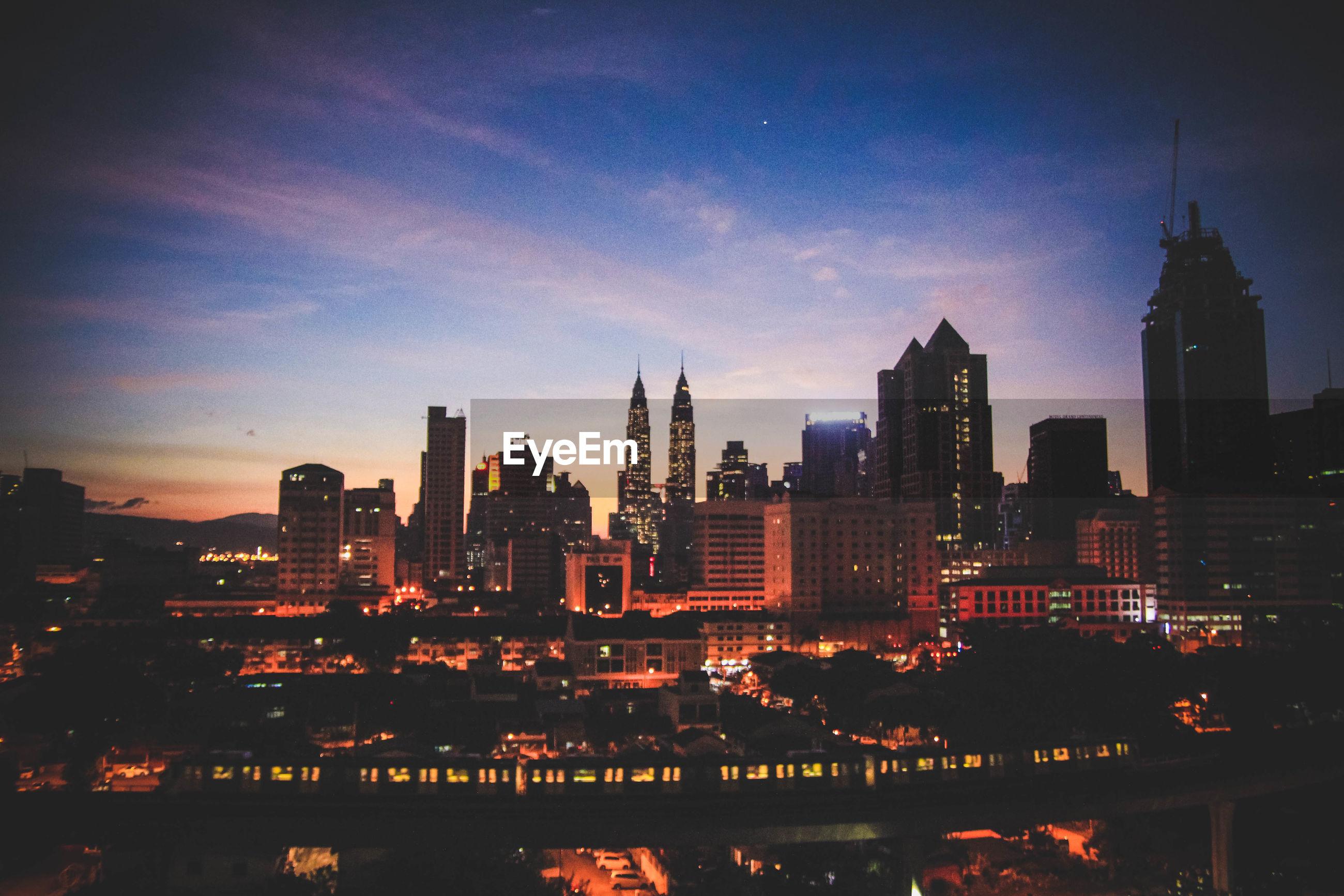CITY LIT UP AGAINST SKY