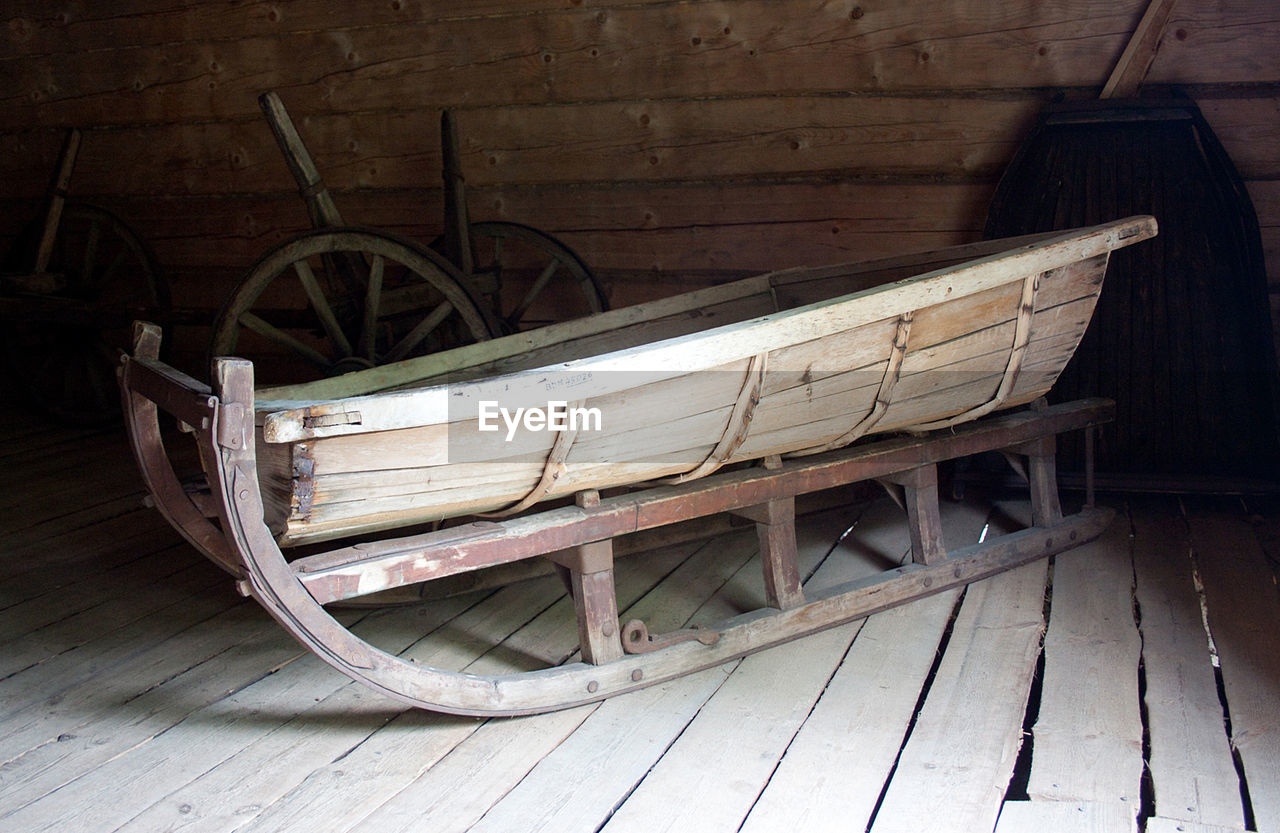 wood - material, no people, transportation, wood, wheel, cart, architecture, mode of transportation, day, old, indoors, seat, built structure, rocking chair, absence, hardwood floor, empty, flooring, wagon wheel
