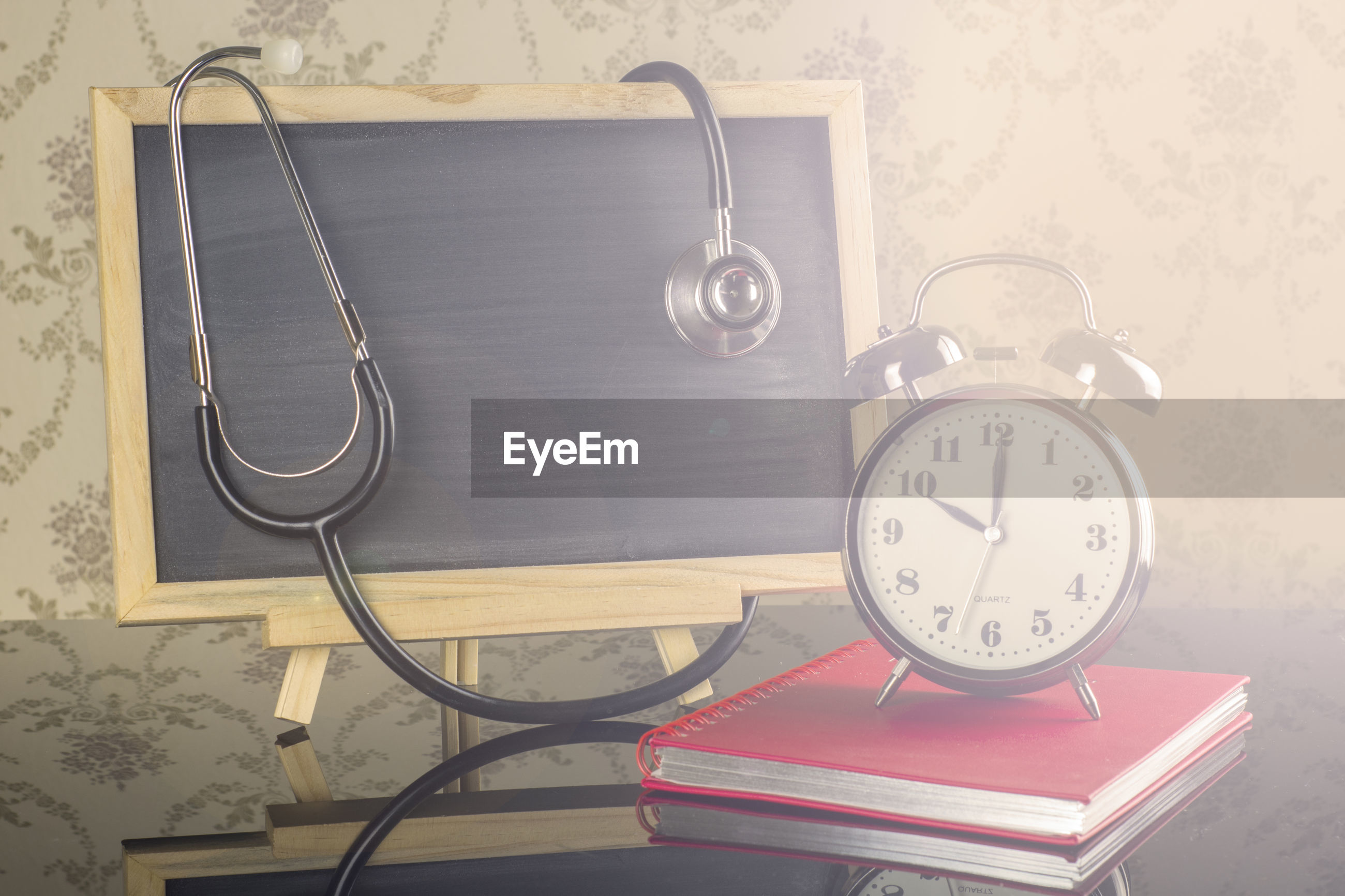 Close-up of alarm clock with blackboard and stethoscope on table