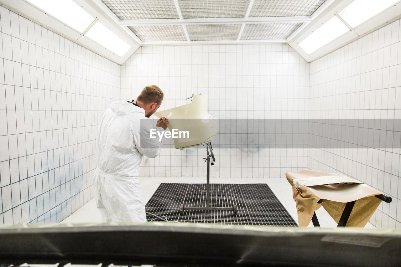 Rear view of man applying
