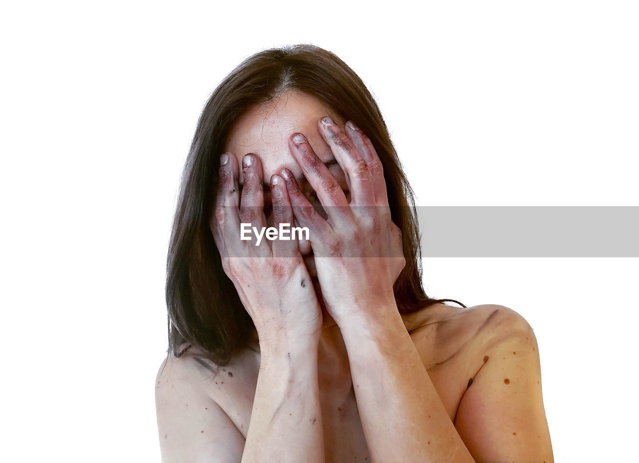 Shirtless woman with hands covering face against white background