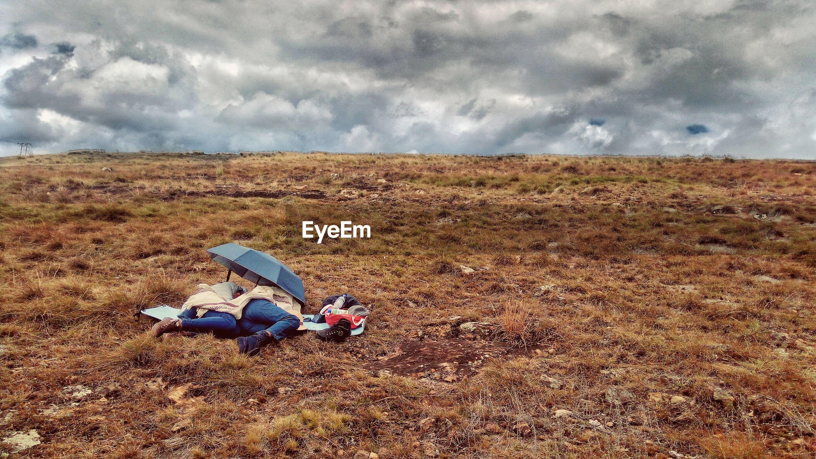 Women under umbrella sleeping on field against cloudy sky