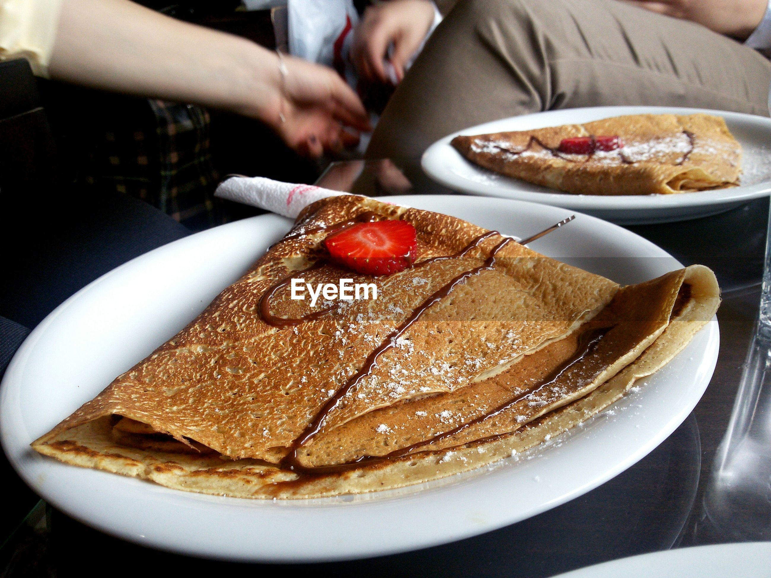 High angle view of crepe with chocolate sauce and strawberry served on table