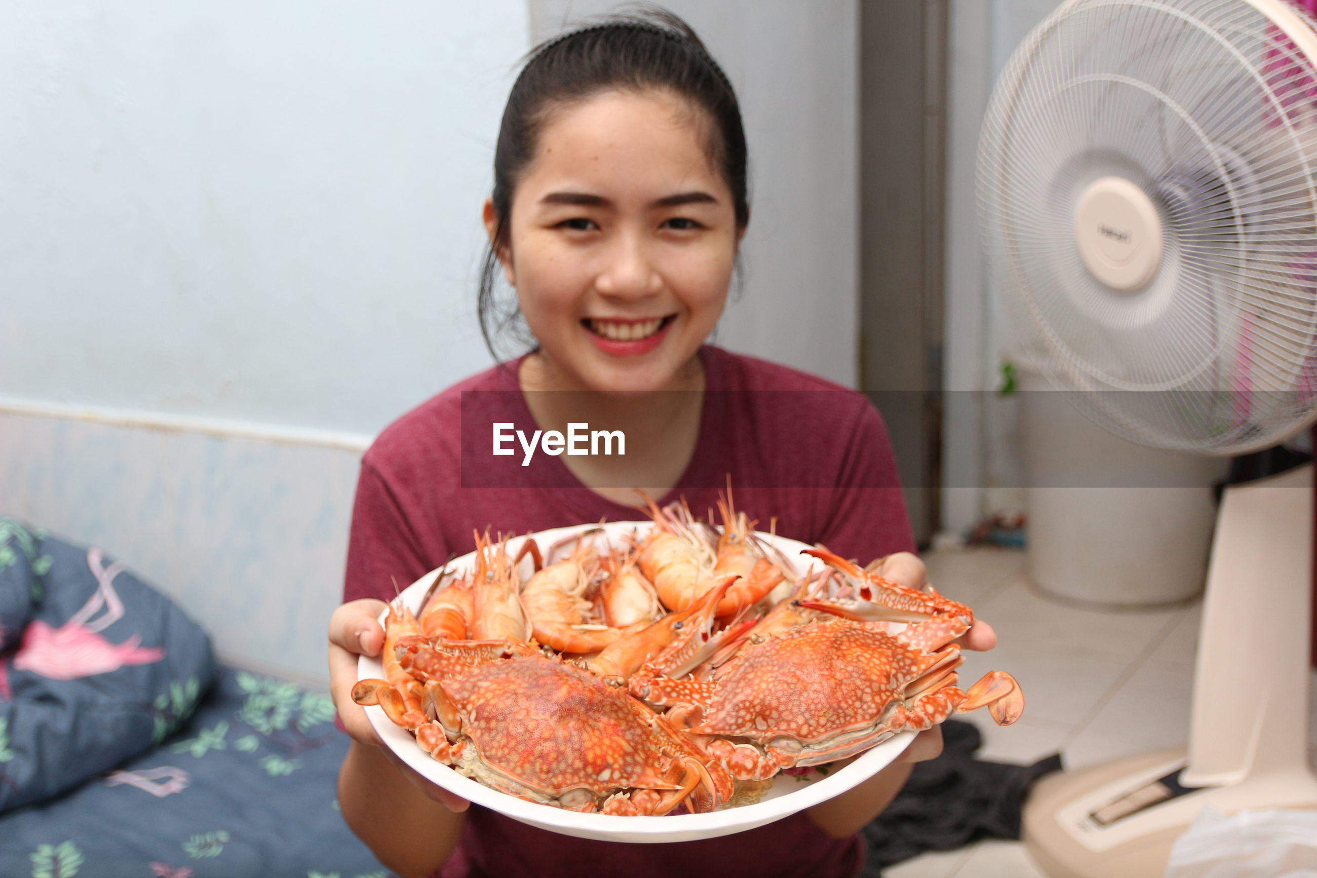 Portrait of smiling woman holding seafood