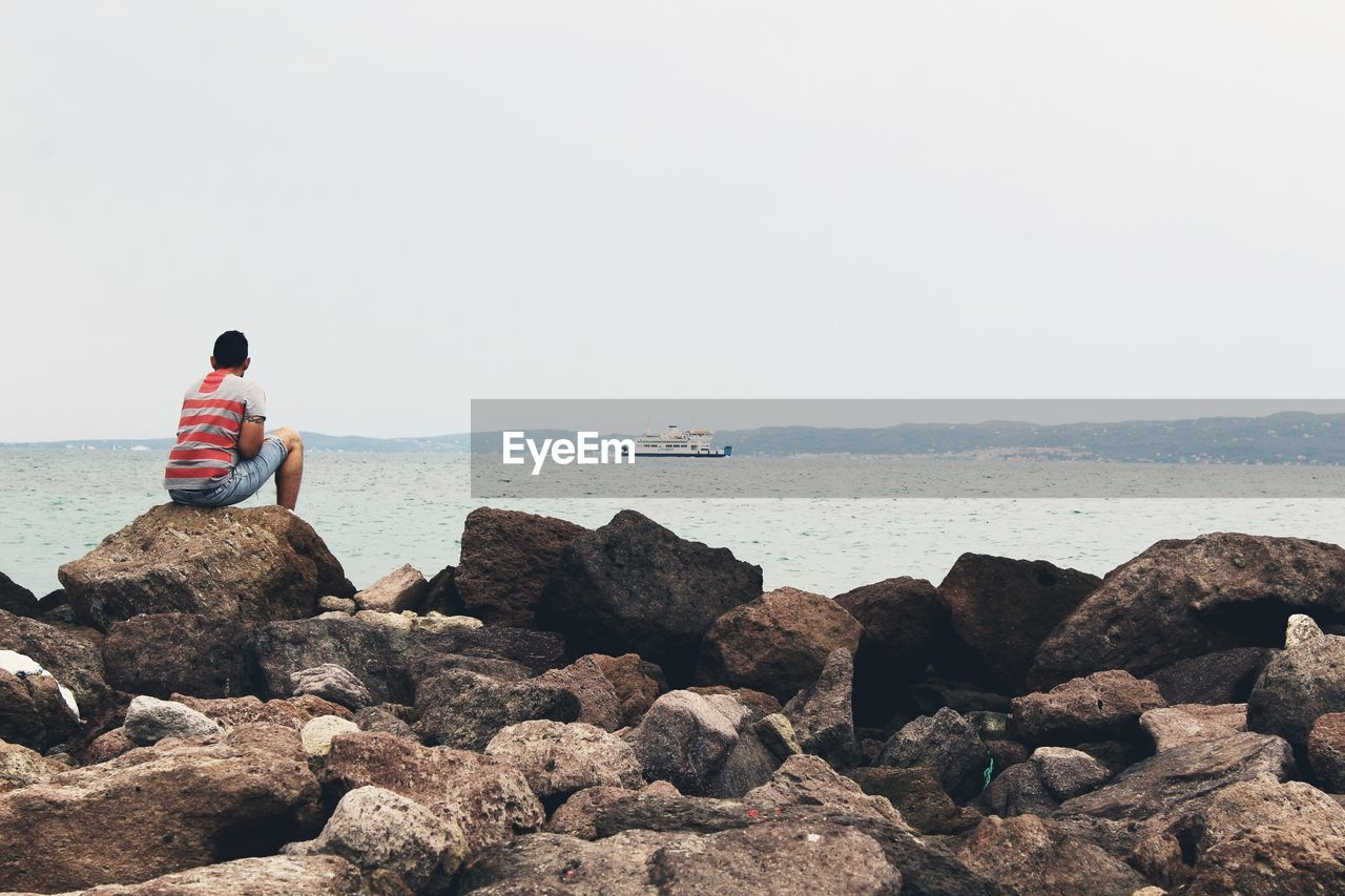 Rear View Of Mid Adult Man Looking At Sea While Sitting On Rock Against Sky