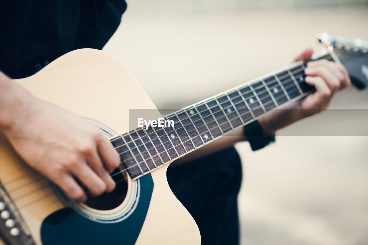 Cropped image of street musician playing guitar